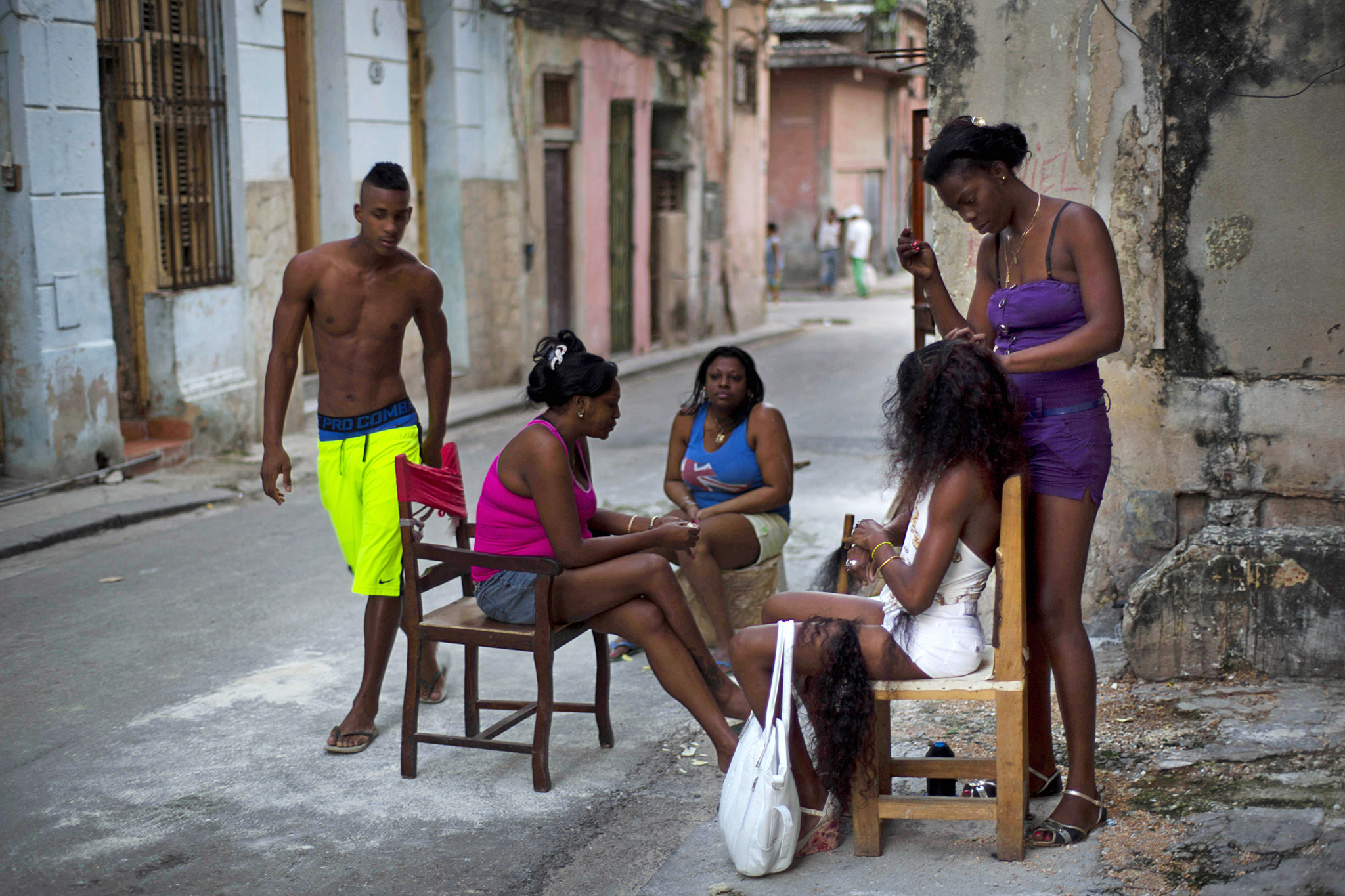 Hairdresser Lisandra works on a woman's extensions as others wait their turn in Old Havana, Cuba, Tuesday, Jan. 13, 2015. Lisandra attends her clients on the sidewalk outside her home. (AP Photo/Ramon Espinosa)