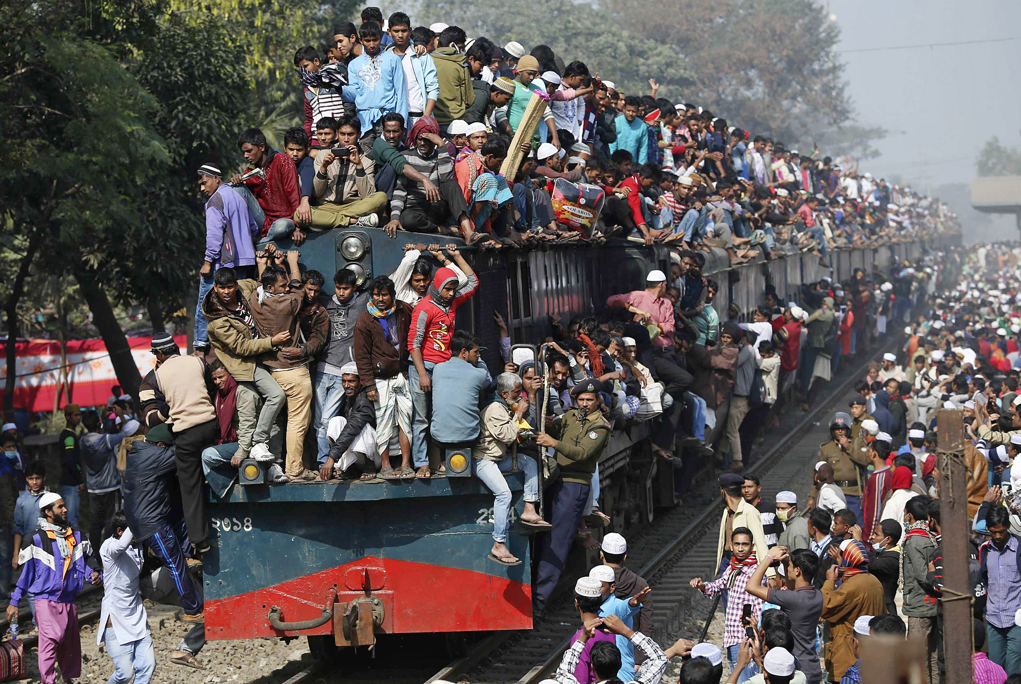 Devotees ride on the roof of a train as they return to the city after attending the final prayers on the first phase of Bishwa Ijtema in Dhaka...Devotees ride on the roof of a train as they return to the city after attending the final prayers on the first phase of Bishwa Ijtema in Dhaka January 11, 2015. Hundreds of thousands of pilgrims congregated in the Bangladeshi capital Dhaka as the first phase of this year's Bishwa Ijtema, one of the biggest Islamic gatherings in the world after the Haj in Saudi Arabia, came to an end. Picture taken January 11, 2015.