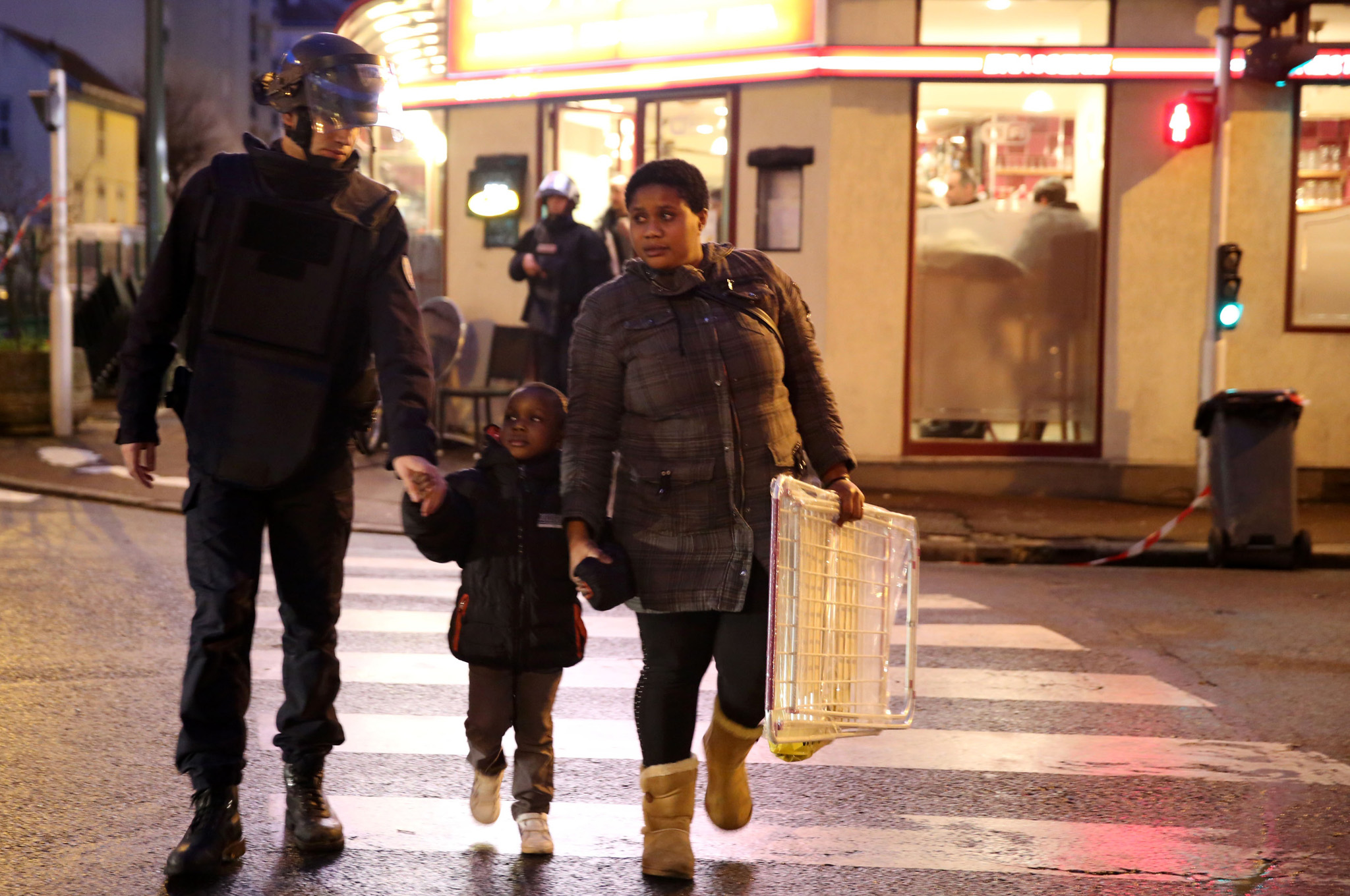 Emergency Services Attend Further Hostage Situation In Kosher Deli...PARIS, FRANCE - JANUARY 09:  Police escort a child and woman as they mobilize at the hostage situation at Port de Vincennes on January 9, 2015 in Paris, France. According to reports at least five people have been taken hostage in a kosher deli in the Port de Vincennes area of Paris. A huge manhunt for the two suspected gunmen in Wednesday's deadly attack on Charlie Hebdo magazine has entered its third day.  (Photo by Dan Kitwood/Getty Images)