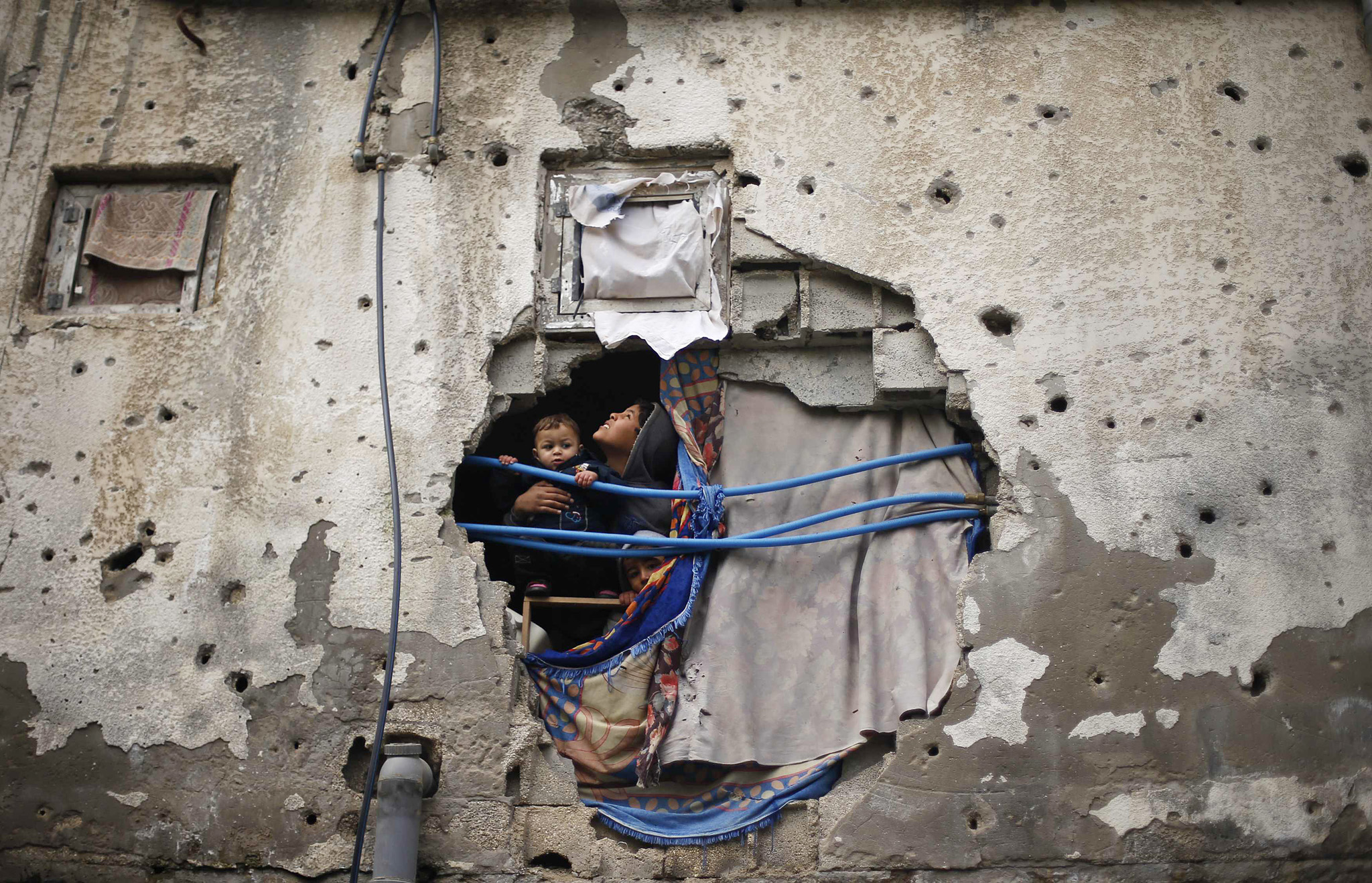Palestinian children look out through a hole covered with a blanket in their family house, that witnesses said was damaged by Israeli shelling during a 50-day war last summer, in the east of Gaza City January 7, 2015. Heavy rains and near-freezing temperatures in the approaching storm threatened to deepen the misery in the Gaza Strip, where streets are still strewn with wreckage from a 50-day war with Israel last summer, thousands live in U.N. shelters and damaged homes and the power is on only six hours a day.  REUTERS/Suhaib Salem (GAZA - Tags: POLITICS CIVIL UNREST TPX IMAGES OF THE DAY)