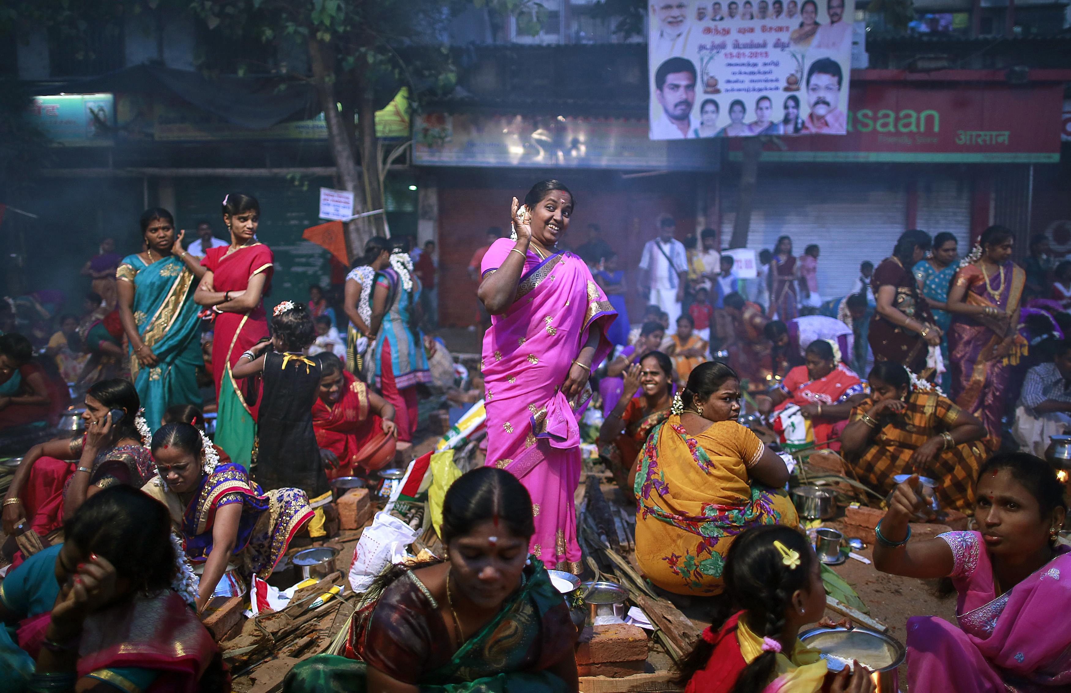 A devotee reacts to smoke as others prepare ritual rice dishes to offer to the Hindu Sun God as they attend Pongal celebrations at a slum in Mumbai...A devotee reacts to smoke as others prepare ritual rice dishes to offer to the Hindu Sun God as they attend Pongal celebrations at a slum in Mumbai January 15, 2015. REUTERS/Danish Siddiqui (INDIA - Tags: SOCIETY RELIGION TPX IMAGES OF THE DAY)