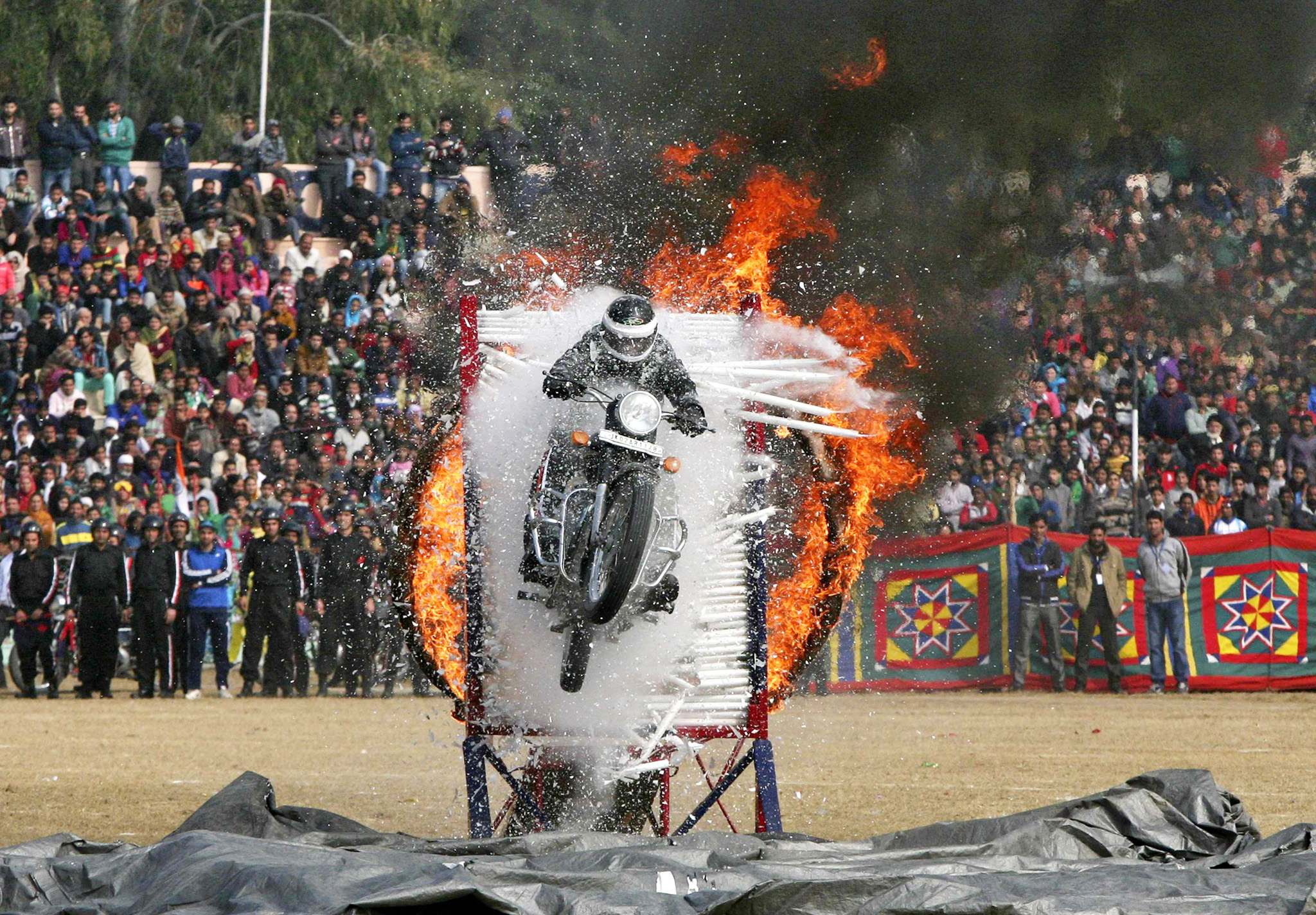 Indian policeman performs a stunt on motorcycle during the Republic Day parade in Jammu...An Indian policeman performs a stunt on his motorcycle during the Republic Day parade in Jammu January 26, 2015. India celebrated its 66th Republic Day on Monday. REUTERS/Mukesh Gupta