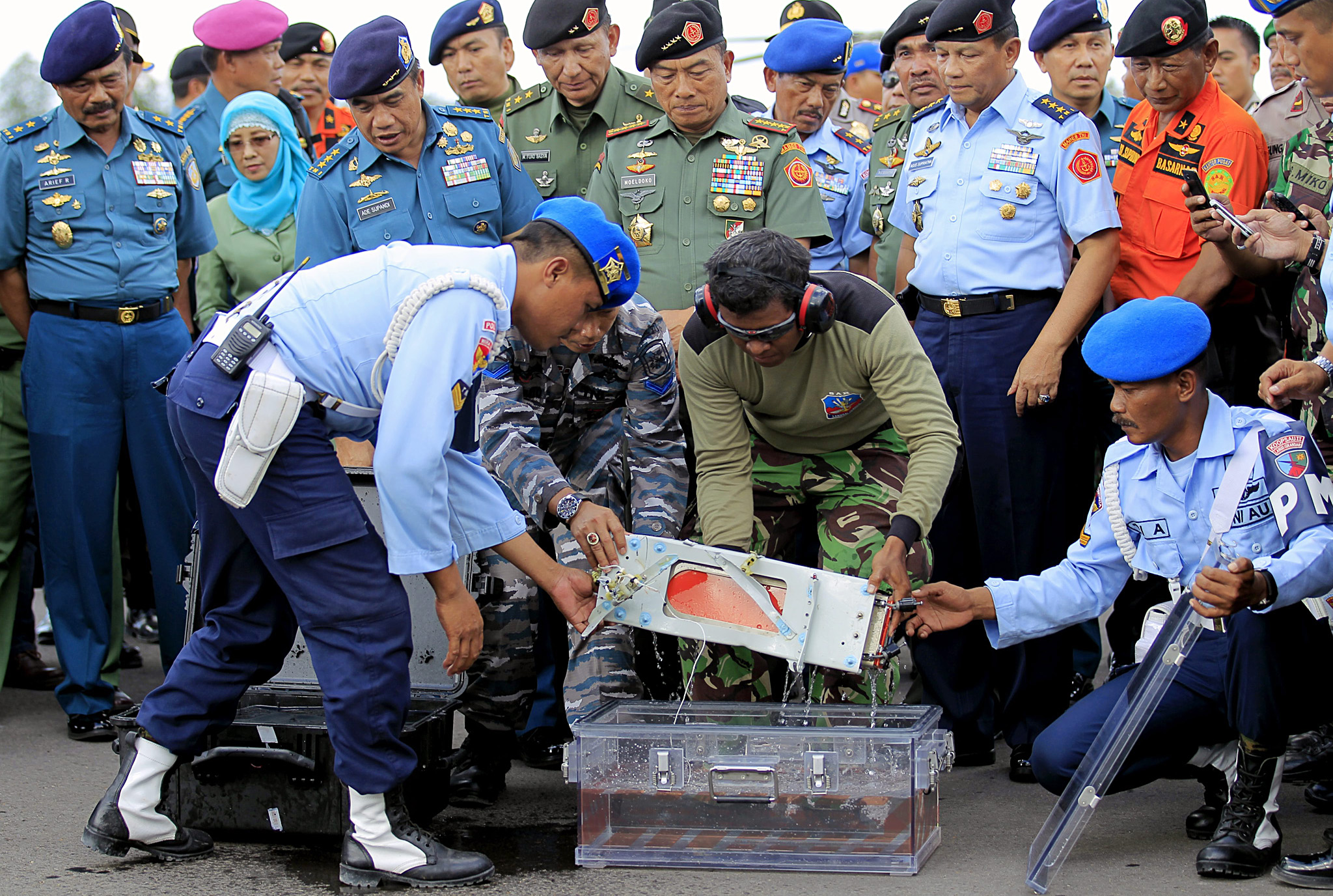 Recovery mission for crashed AirAsia plane in Pangkalan Bun Indonesia...epa04556615 Indonesian officers put the flight data recorder during the recovery mission at Iskandar Military Airport in Pangkalan Bun, Central Borneo, Indonesia, 12 January 2015. The cockpit voice recorder from the AirAsia plane that crashed into the Java Sea has been found. The device was found near the location of the flight data recorder retrieved earlier in the day, search operation director Suryadi Supriyadi said.  EPA/BAGUS INDAHONO