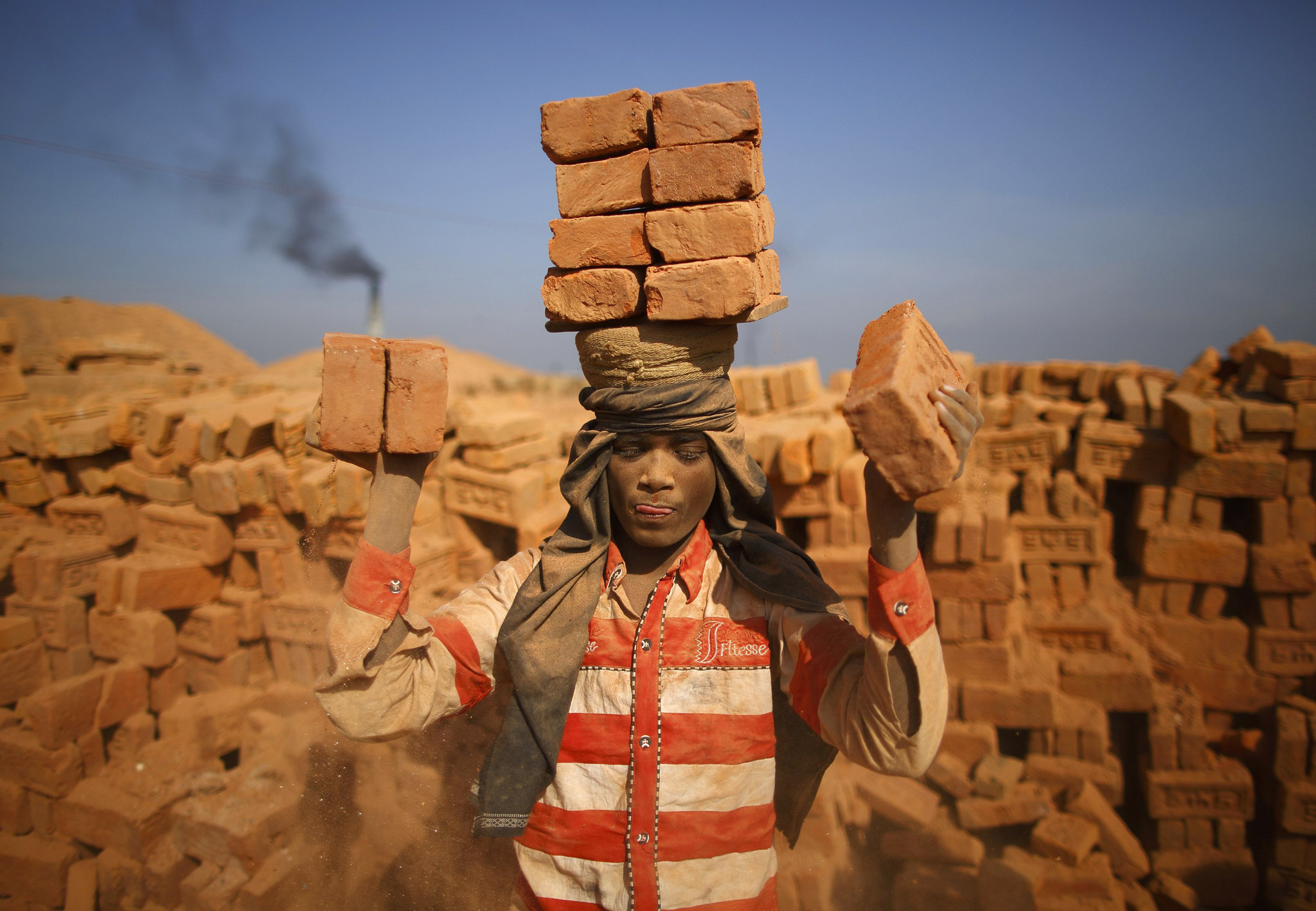 A worker stack bricks on his head at a brick factory in Lalitpur...A worker stack bricks on his head at a brick factory in Lalitpur