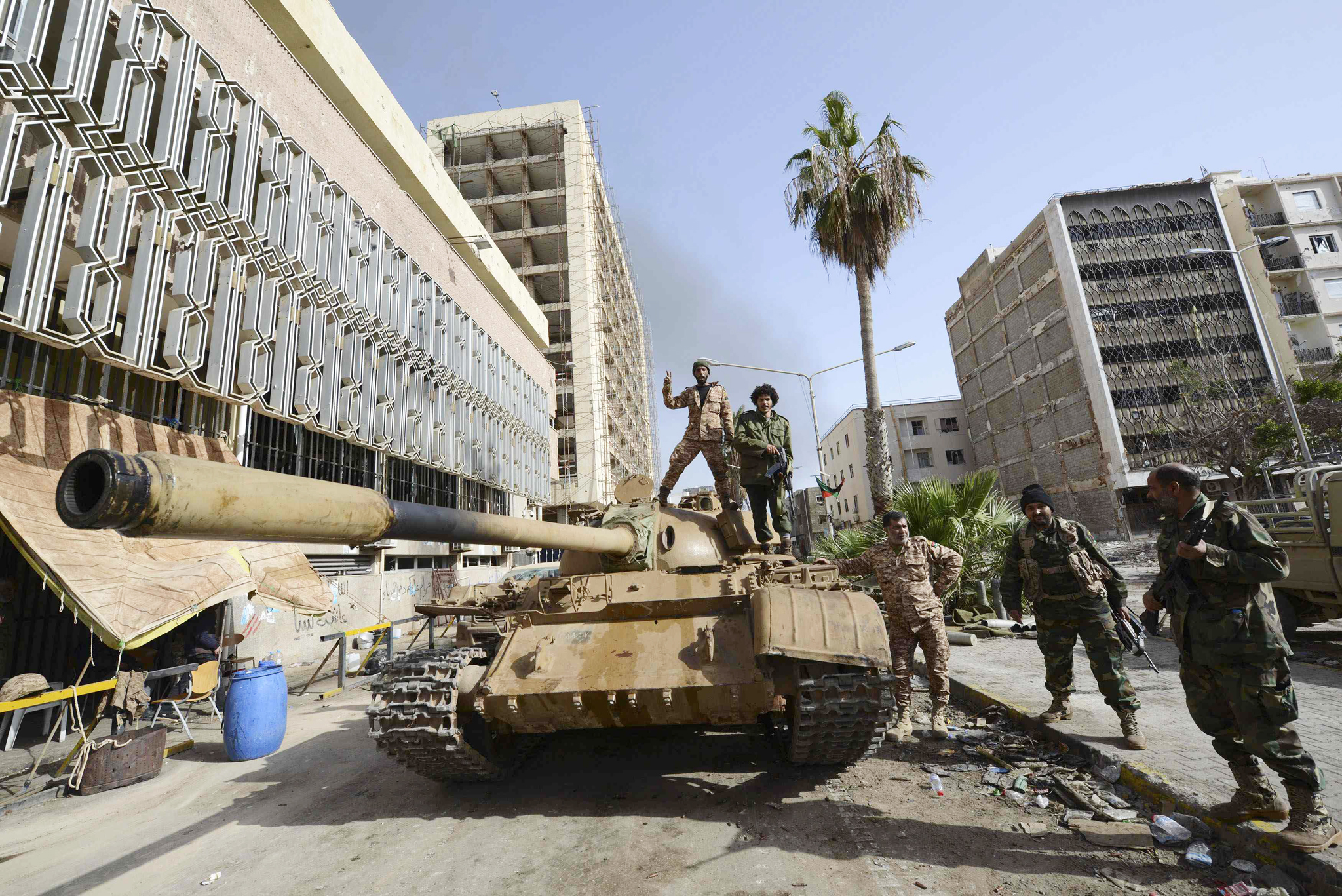 Members of the Libyan pro-government forces, backed by locals, gather on a tank outside the Central Bank, near Benghazi port...Members of the Libyan pro-government forces, backed by locals, gather on a tank outside the Central Bank, near Benghazi port, January 21, 2015. The area has been the scene of heavy battles for weeks against the Shura Council of Libyan Revolutionaries, an alliance of ex anti-Gaddafi rebels, who have joined forces with Islamist group Ansar al-Sharia A parliament set up in Libya to rival the elected assembly has suspended U.N.-sponsored peace talks because of what it called fresh violence from the country's recognized government, a spokesman said on Wednesday.  REUTERS/Esam Omran Al-Fetori (LIBYA - Tags: CIVIL UNREST POLITICS)