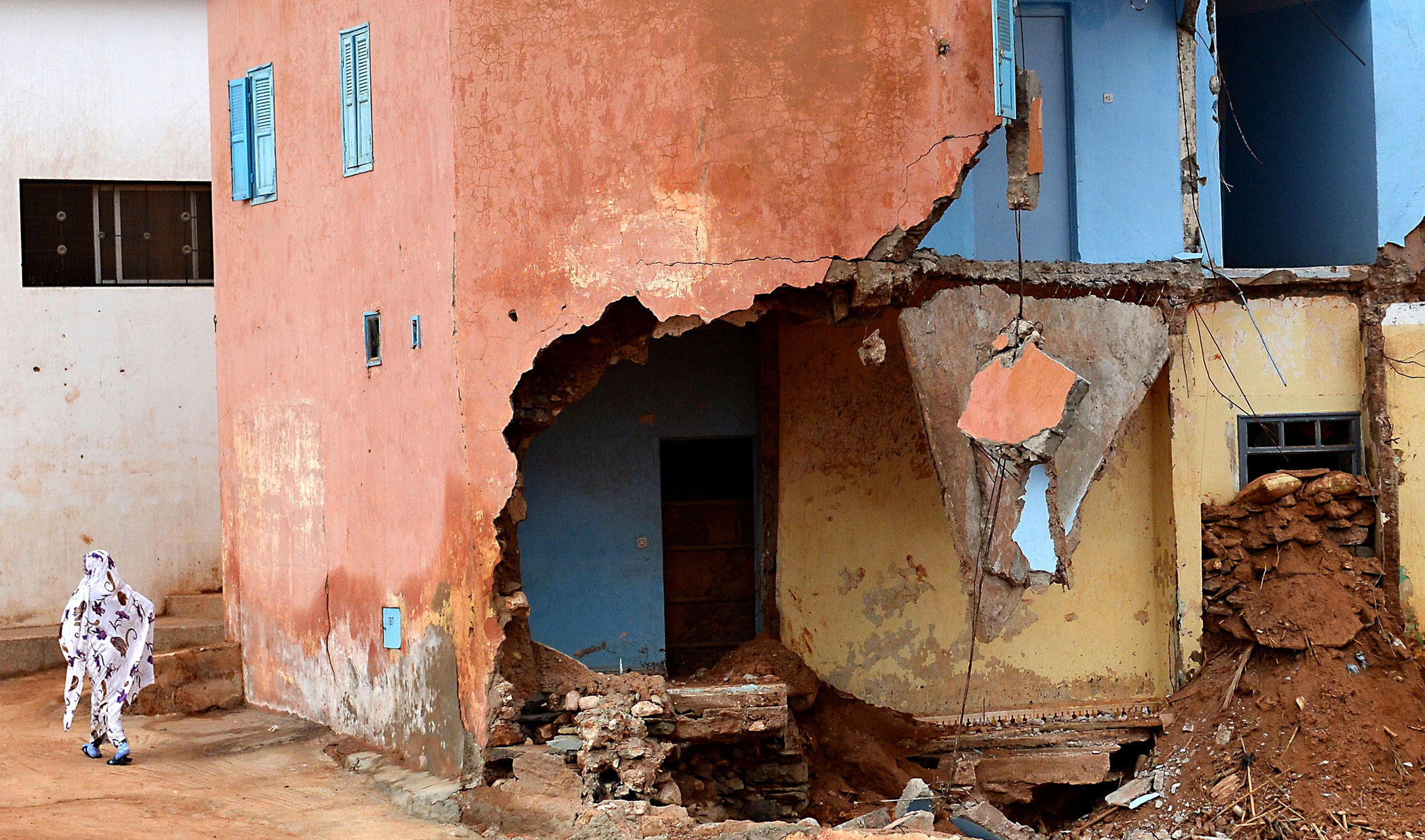 A woman walks past houses that were heavily damaged by flash floods two month earlier in the coastal Moroccan village of Aglou, north of Sidi Ifni on January 12, 2015. The floods, that were described by the residents as the heaviest storms to hit southern Morocco in decades, killed at least 32 people and left others homeless. AFP PHOTO / FADEL SENNAFADEL SENNA/AFP/Getty Images