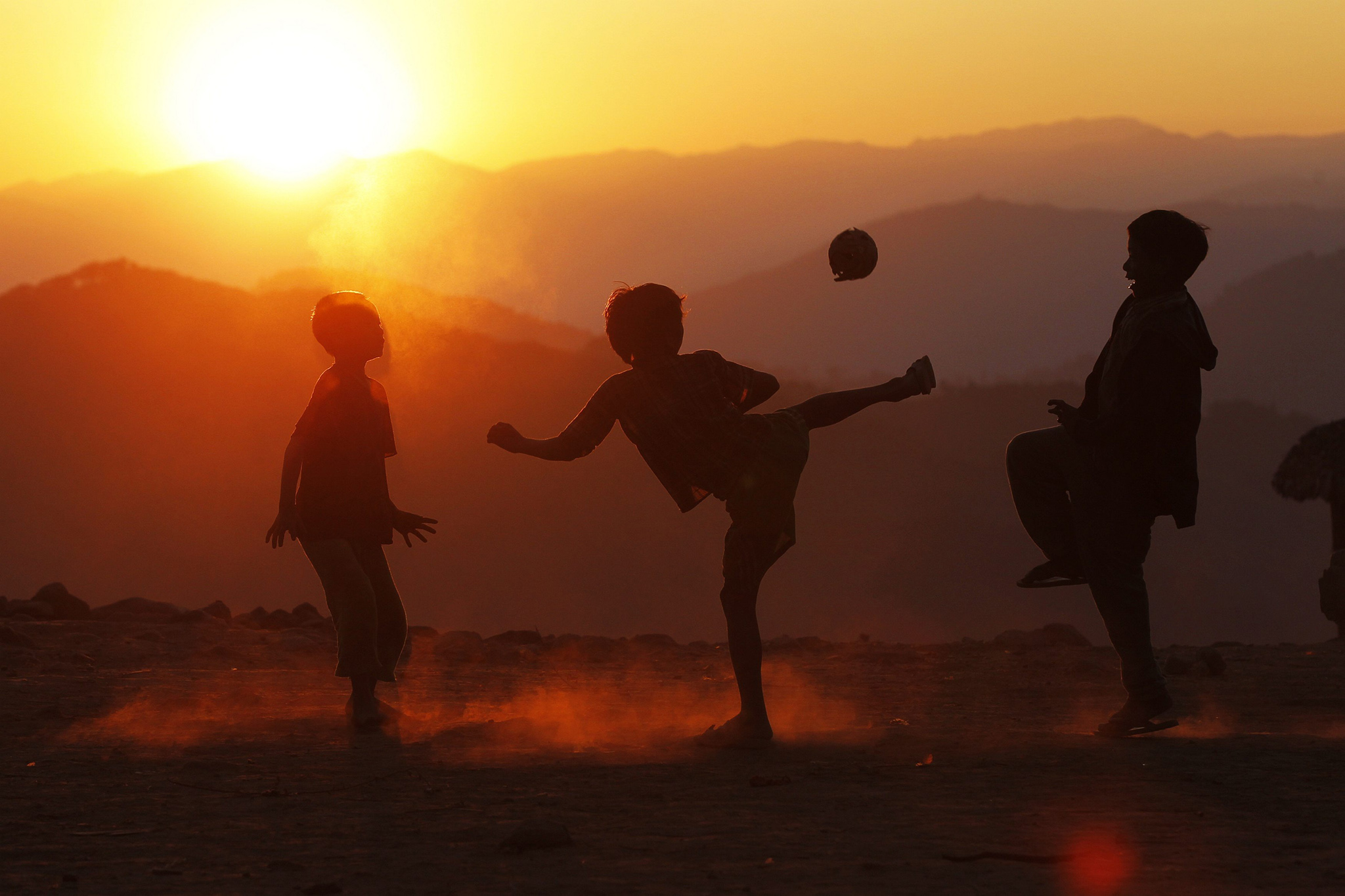 Boys play with a ball in Yansi village, Donhe township in the Naga Self-Administered Zone...Boys play with a ball at sunset in Yansi village, Donhe township in the Naga Self-Administered Zone in northwest Myanmar December 25, 2014. On Myanmar's mountainous frontier with India live the Naga, a group of tribes historically known as warriors who kept the heads of enemies they killed. In Myanmar, around 120,000 people live in the Naga Self-Administered Zone in Sagaing Division where they survive mainly by subsistence farming and hunting. Cultural practices are changing - for example, younger men now wear trousers rather than traditional loincloths - although many Naga communities remain impoverished and inaccessible by road. The Naga speak dozens of languages and many of those in Myanmar use Burmese as a lingua franca. REUTERS/Soe Zeya Tun (MYANMAR - Tags: AGRICULTURE SOCIETY FOOD TPX IMAGES OF THE DAY)     ATTENTION EDITORS: PICTURE 24 OF 24 FOR WIDER IMAGE PACKAGE 'HUNTING WITH MYANMAR'S NAGA'    SEARCH 'NAGA SOE ZEYA' FOR ALL IMAGES