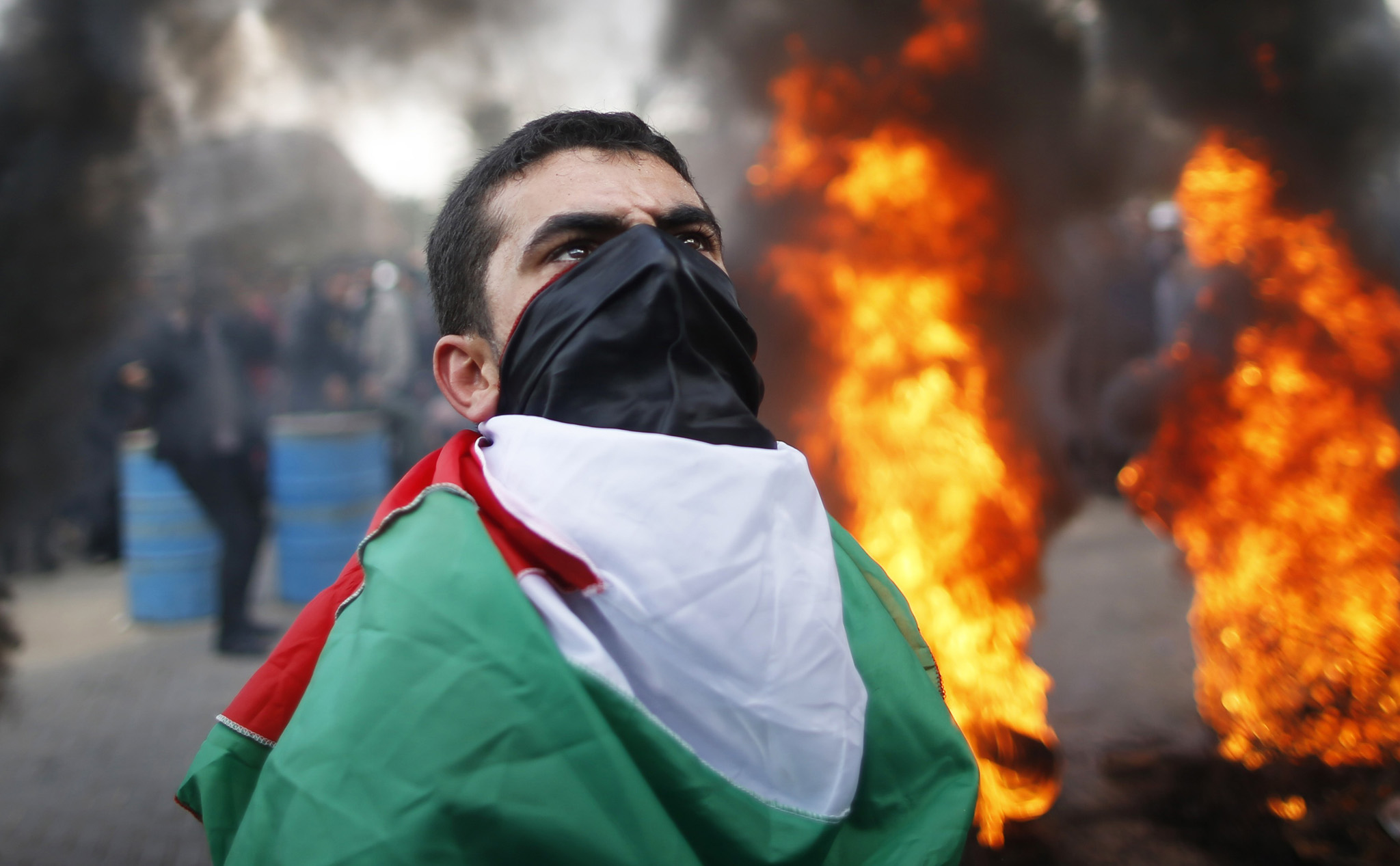 A Palestinian draped in a Palestinian flag stands next to burning tyres during a protest against the decision by the main U.N. aid agency to suspend payments to tens of thousands of Palestinians for repairs to their homes damaged in last summer's war, outside the headquarters of the United Nations Special Coordinator in Gaza City January 28, 2015. Dozens of Palestinians, whose homes were destroyed and damaged in the summer war, attacked the office of the United Nations Special Coordinator in Gaza, to protest the decision by a key United Nations organisation to suspend its cash aid to them. Some burnt tyres outside the gate while others tried to storm in through climbing the outer walls. Some hurled stones into the headquarters.