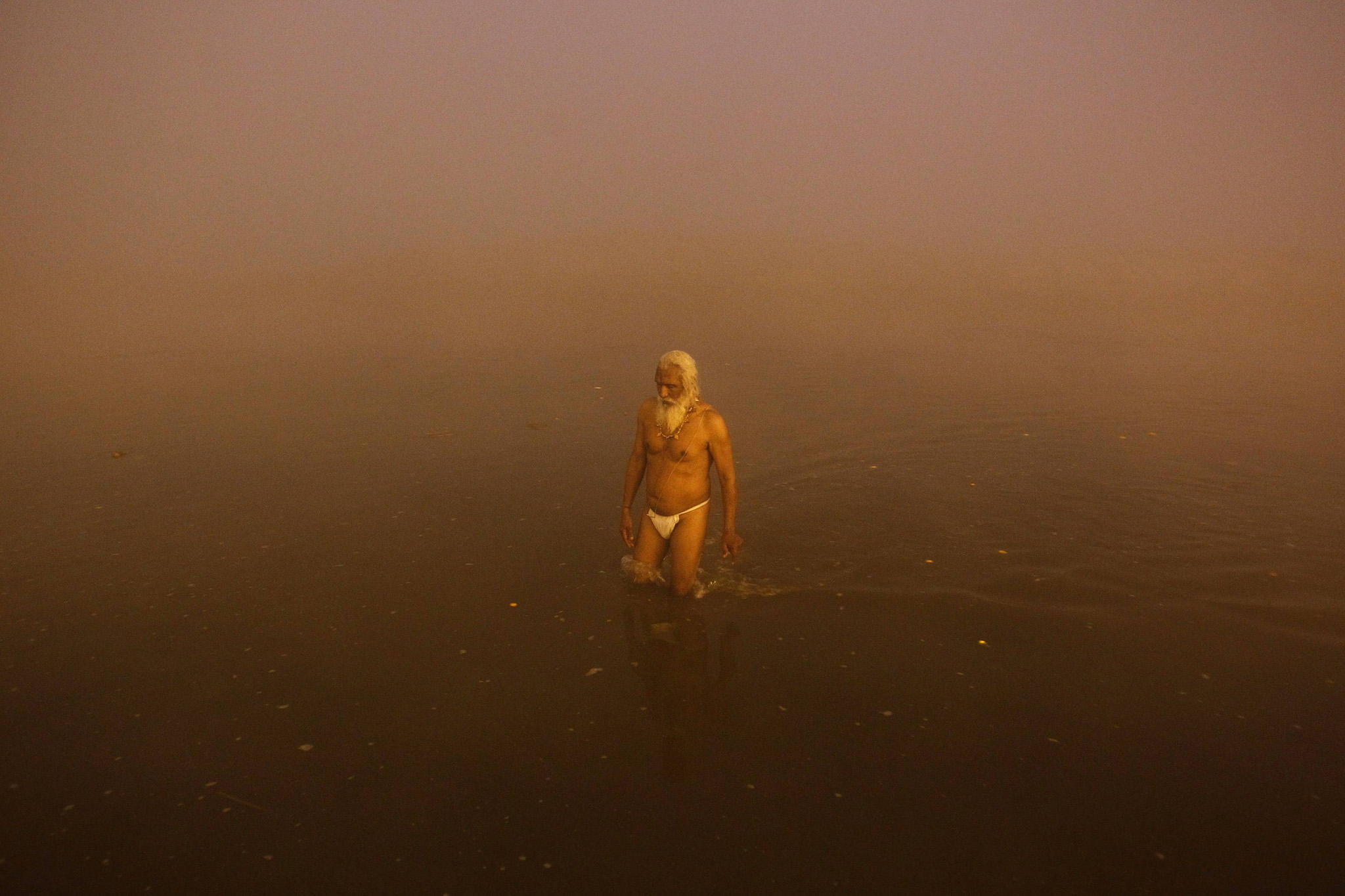 A Sadhu or a Hindu holy man walks after taking a holy bath at Sangam, the confluence of the Ganges, Yamuna and Saraswati rivers, on a foggy winter morning, on the occasion of Makar Sankranti festival in the northern Indian city of Allahabad January 14, 2015. Makar Sankranti is an auspicious festival celebrated by Hindus across the country that marks the start of the harvest season.