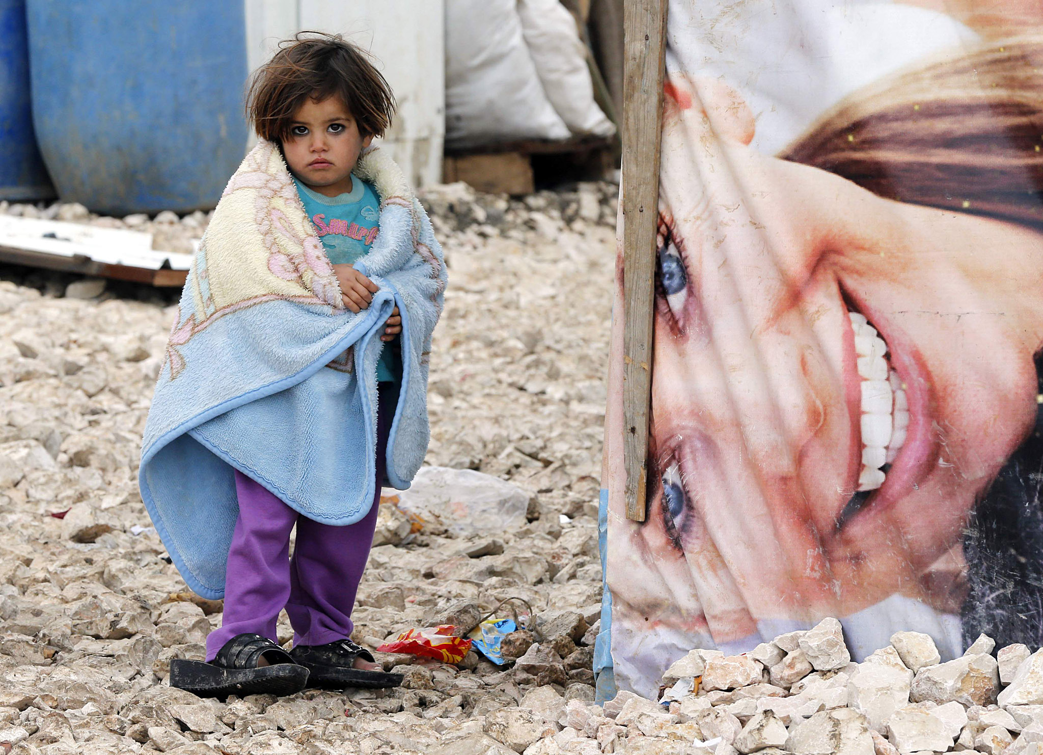 A Syrian refugee girl covers herself with a blanket as she stands outside tents at a makeshift settlement in Bar Elias in the Bekaa valley...A Syrian refugee girl covers herself with a blanket as she stands outside tents at a makeshift settlement in Bar Elias in the Bekaa valley January 5, 2015. Lebanon enforced new immigration controls at the Syrian border on Monday in a move to gain control of the steady stream of refugees from its much larger neighbour.   REUTERS/Mohamed Azakir (LEBANON - Tags: SOCIETY IMMIGRATION CIVIL UNREST CONFLICT POLITICS)