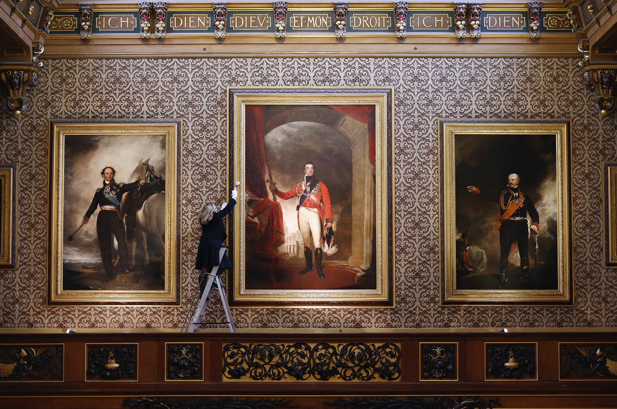 Press preview for Waterloo at Windsor: 1815-2015 Exhibition...WINDSOR, ENGLAND - JANUARY 28: A member of the Royal Collection staff poses besides a portrait of the Duke of Wellington in the Waterloo Chamber during a press preview for Waterloo at Windsor: 1815-2015 Exhibition at Windsor Castle on January 28, 2015 in Windsor, England. Paintings in the chamber will be on display with objects presented to George IV from the battle of Waterloo, which celebrates it's bicentennial this year. The exhibition opens at Windsor Castle from January 31, to January 13, 2016 as part of the 200th anniversary of the Battle of Waterloo celebrations.  (Photo by Dan Kitwood/Getty Images)