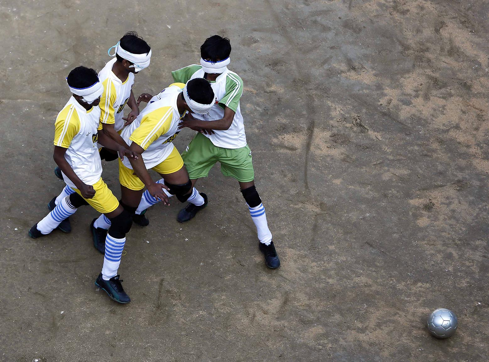Visually impaired students of a school for the blind fight for the ball during a soccer match inside their school in New Delhi