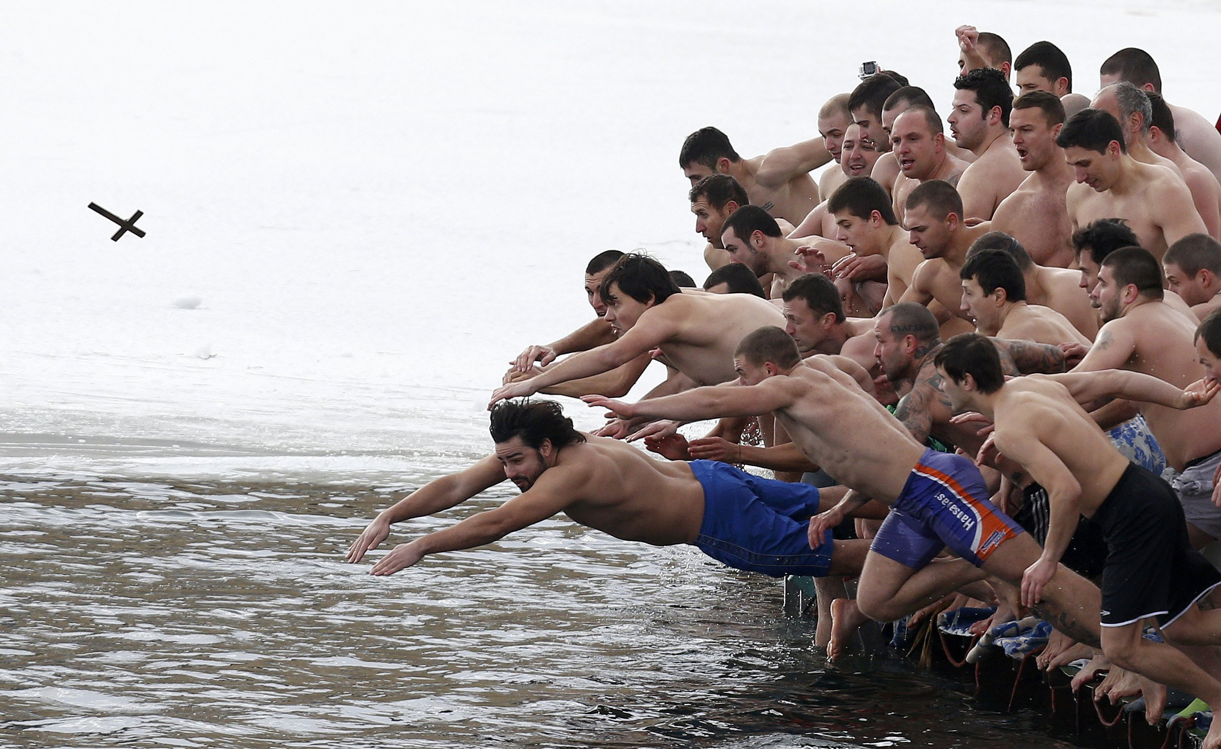 Men jump into the waters of a lake in an attempt to grab a wooden cross on Epiphany Day in Sofia...Men jump into the waters of a lake in an attempt to grab a wooden cross on Epiphany Day in Sofia January 6, 2015. Orthodox priests throughout the country bless the waters by throwing a cross into it as worshippers try to retrieve it. It is strongly believed that catching the cross brings health and prosperity to the person who captures it.    REUTERS/Stoyan Nenov (BULGARIA  - Tags: SOCIETY RELIGION TPX IMAGES OF THE DAY)