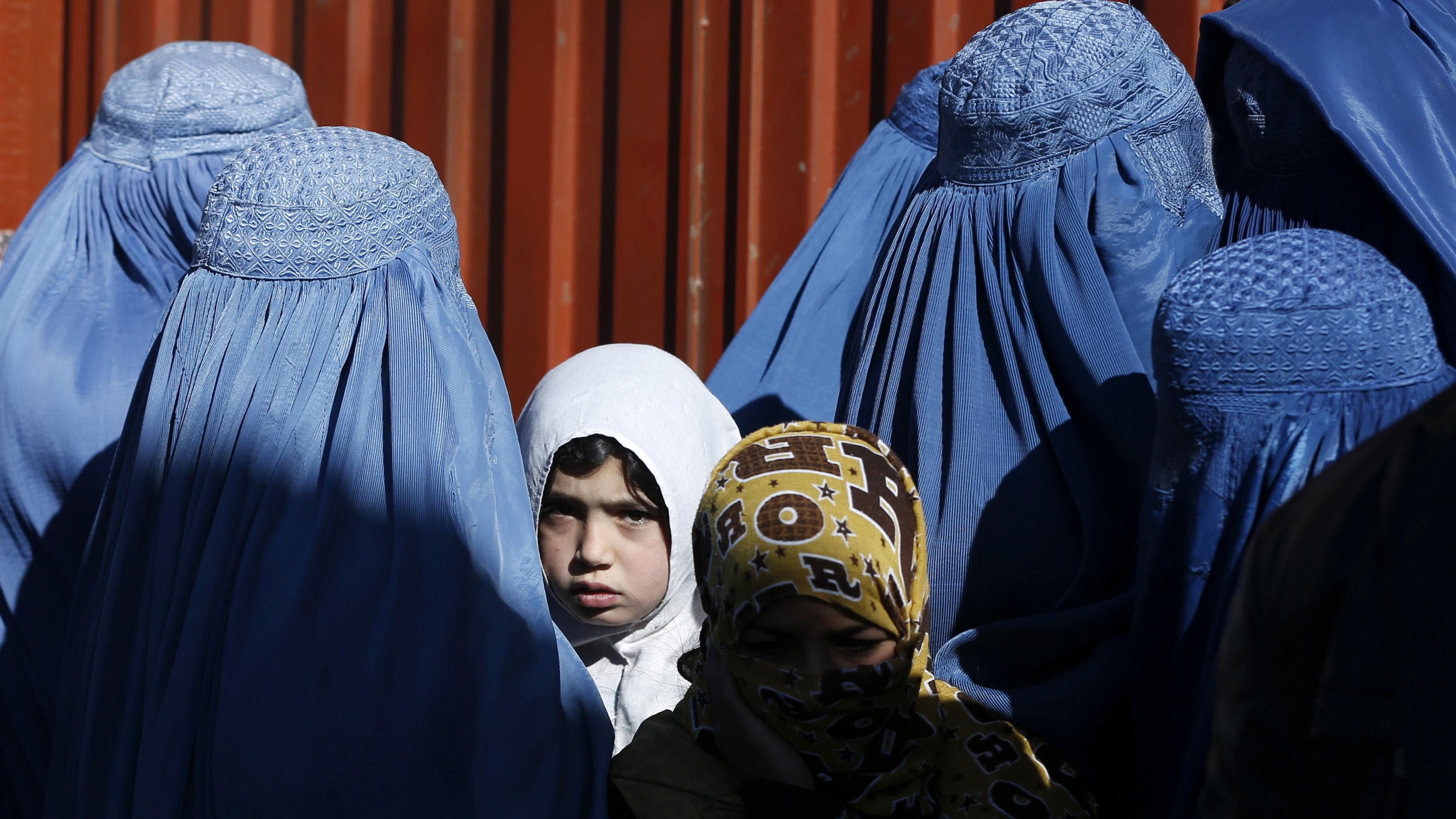 A girl looks on among Afghan women lining up to receive winter relief assistance donated by the UNHCR in Kabul