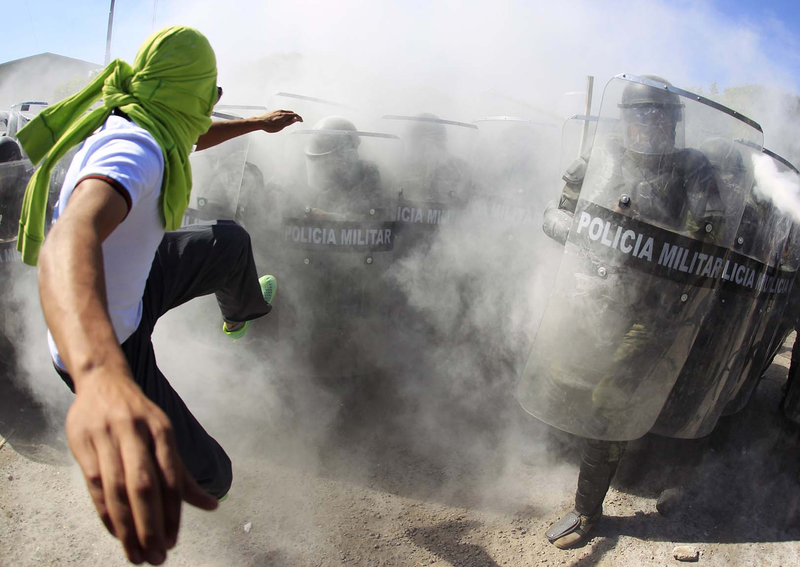 Activist kicks the shields of the military police officers during a demonstration in the military zone of the 27th infantry battalion in Iguala, Guerrero