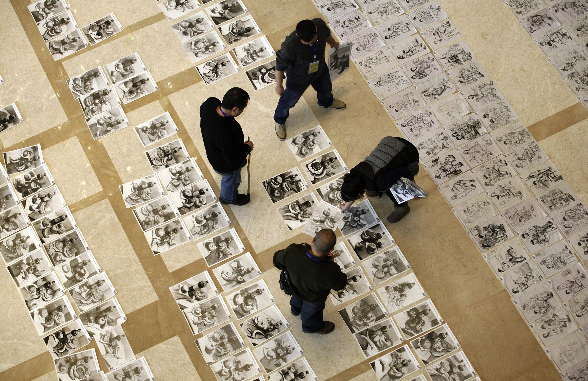 Exam markers inspect students' exam papers for the national college entrance examination to the higher academy of fine arts at the paper inspection site in Xi'an, Shaanxi province, China.
