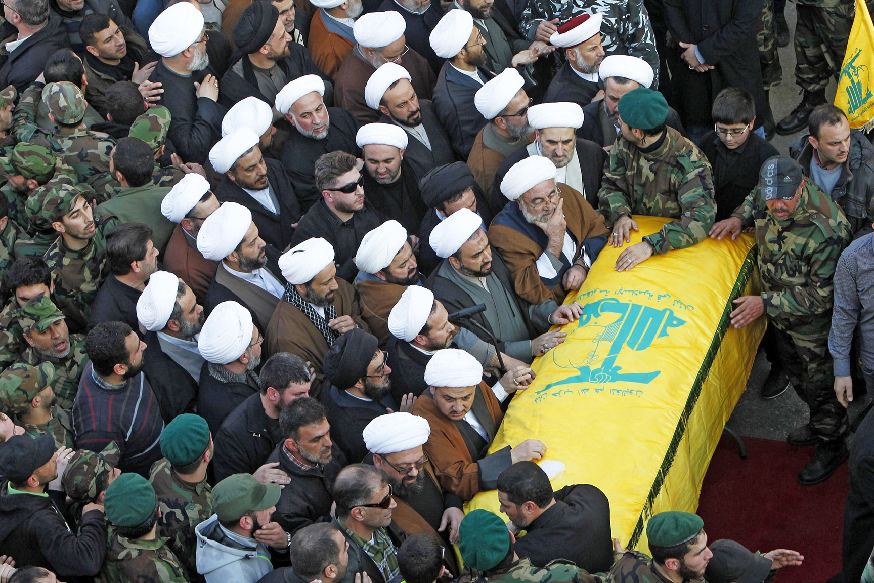 Religious figures along with Hezbollah members and supporters mourn over the coffin of Lebanon's Hezbollah commander Mohamad Issa, known as Abu Issa, during funeral in Arab-Salim