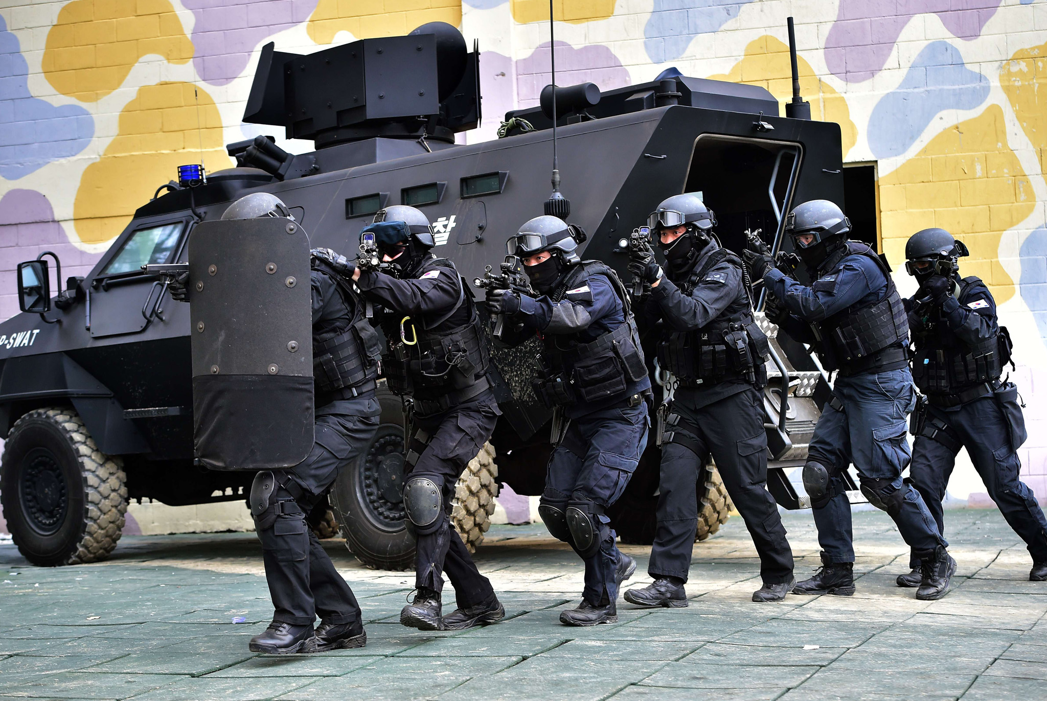 A South Korean police SWAT team members move into a building during an anti-terror drill in Seoul.