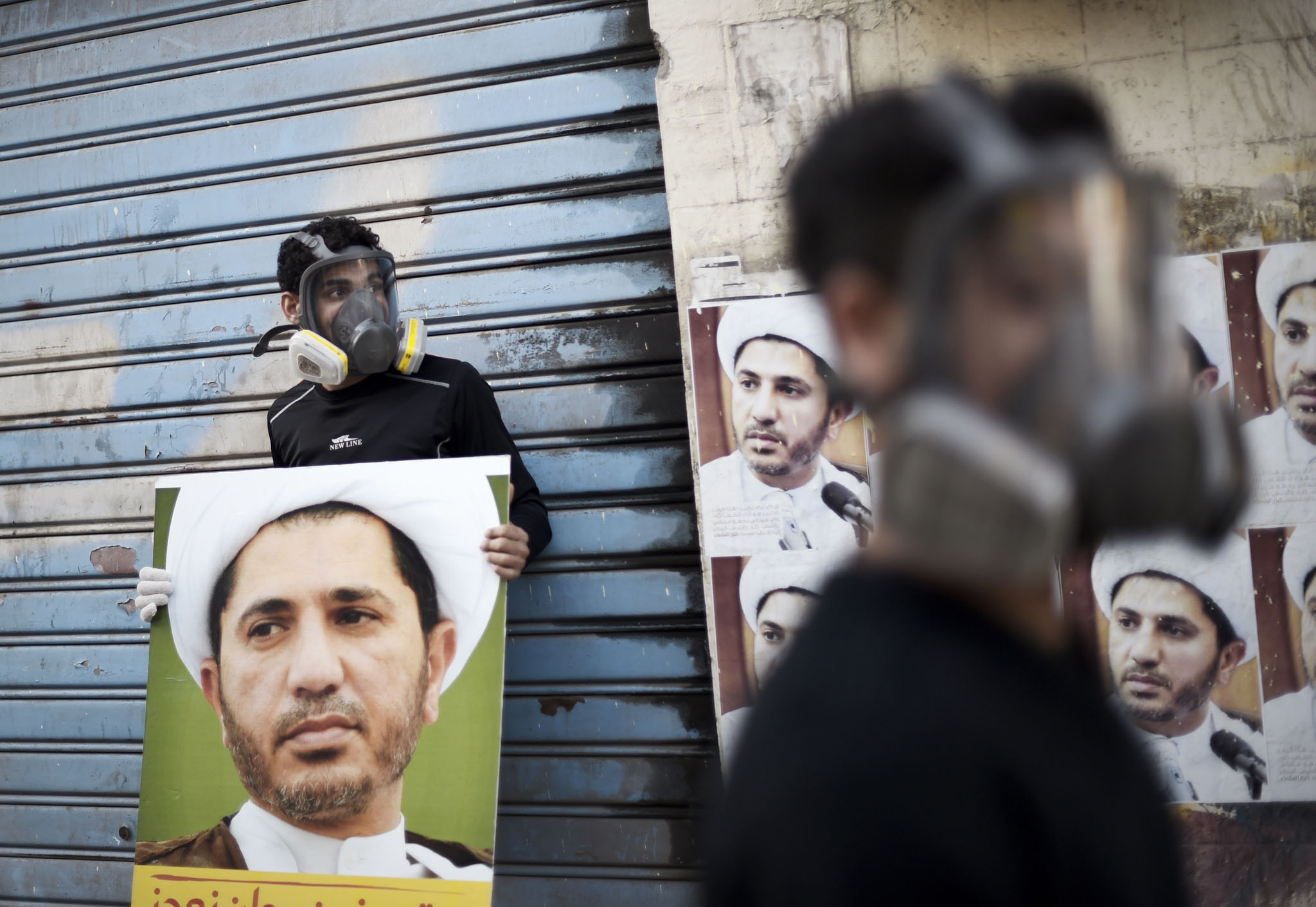 Bahraini protesters wearing gas masks, look on during clashes with police after a demonstration against the arrest of Sheikh Ali Salman (portrait), head of the Shiite opposition movement Al-Wefaq, in Salman's home village of Bilad al-Qadeem, on the outskirts of the capital Manama.