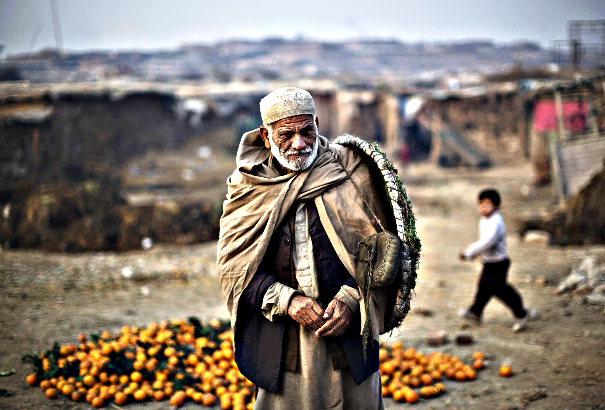 An Afghan refugee who works as a porter at a wholesale fruit an vegetable market walks to his work on the outskirts of Islamabad, Pakistan, Monday, Jan. 5, 2015.