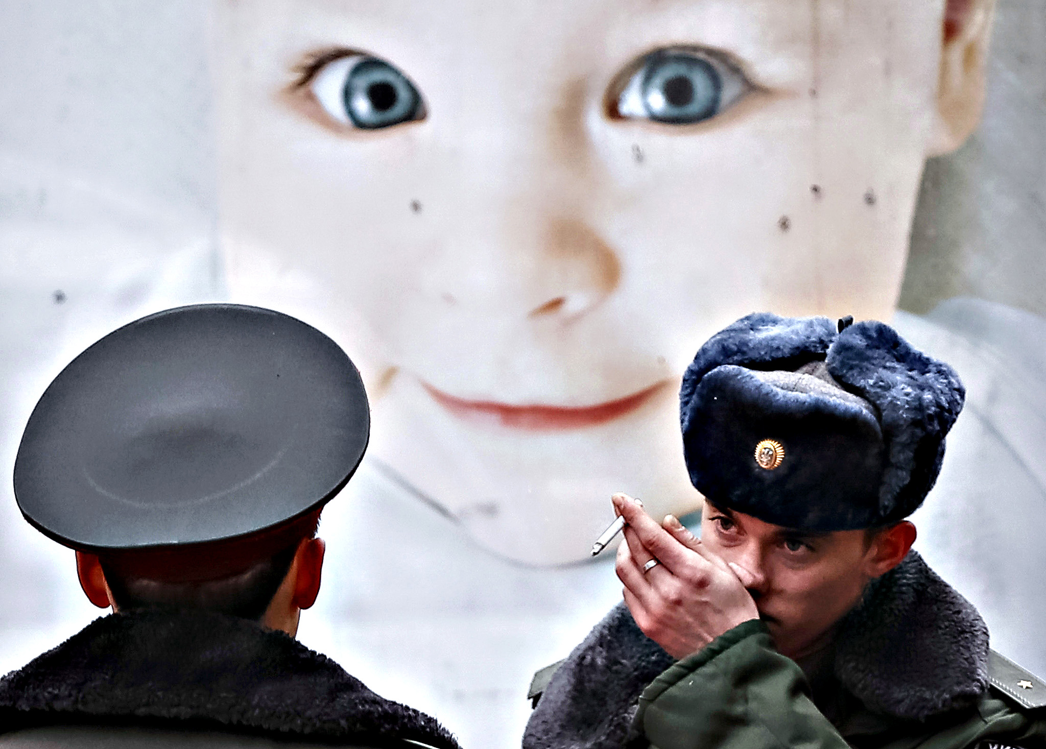 Ukrainian servicemen are seen near a billboard with social advertising in central Kiev, January 15, 2015. Ukraine's parliament voted on Thursday to refresh its front-line forces and resume partial conscription after a top security official warned that Russian forces backing separatist rebels had sharply increased military activity in the east.