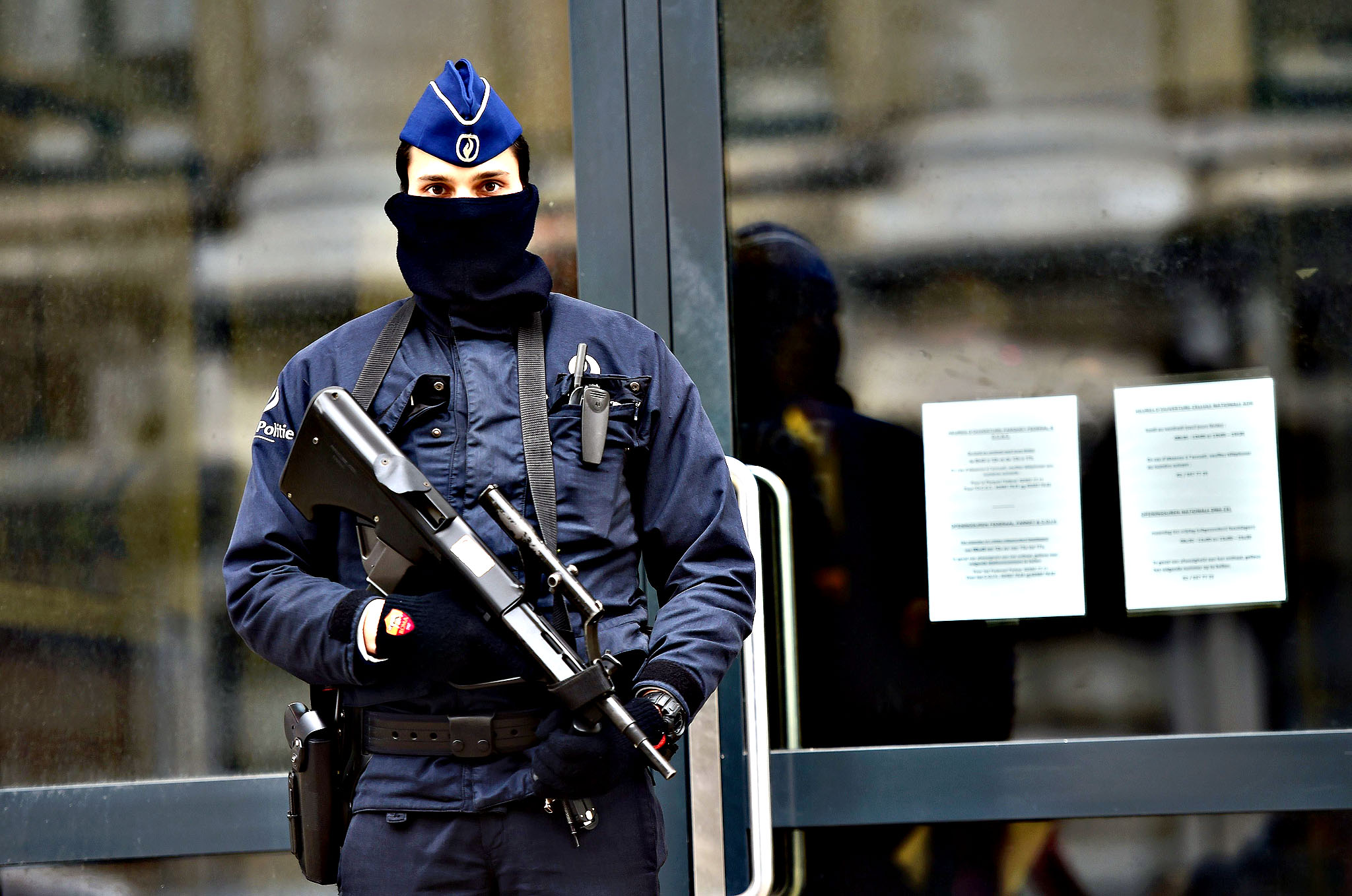 "An armed policeman stands guard at the entrance of Belgium's federal prosecutor office in Brussels, January 16, 2015.  Belgian police arrested 13 people during a dozen raids overnight, smashing plot to kill police officers ""in public roads and in police stations"", prosecutors said."