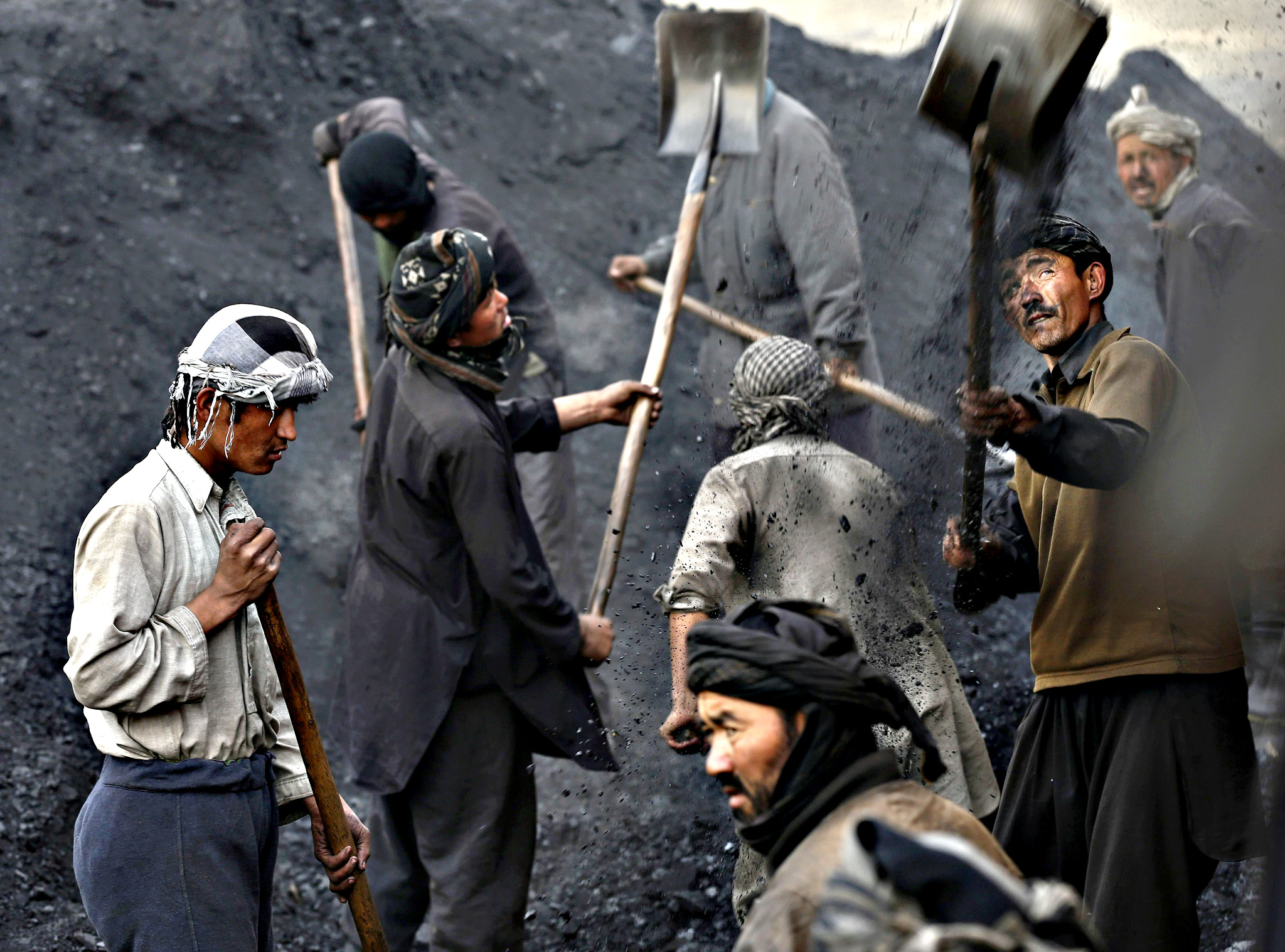 Labourers shovel coal onto a truck at a coal dump site outside Kabul January 19, 2015. Each labourer earns an average of $10 per working day, with most of them coming come from the northern provinces, leaving their families behind to find work in the capital.