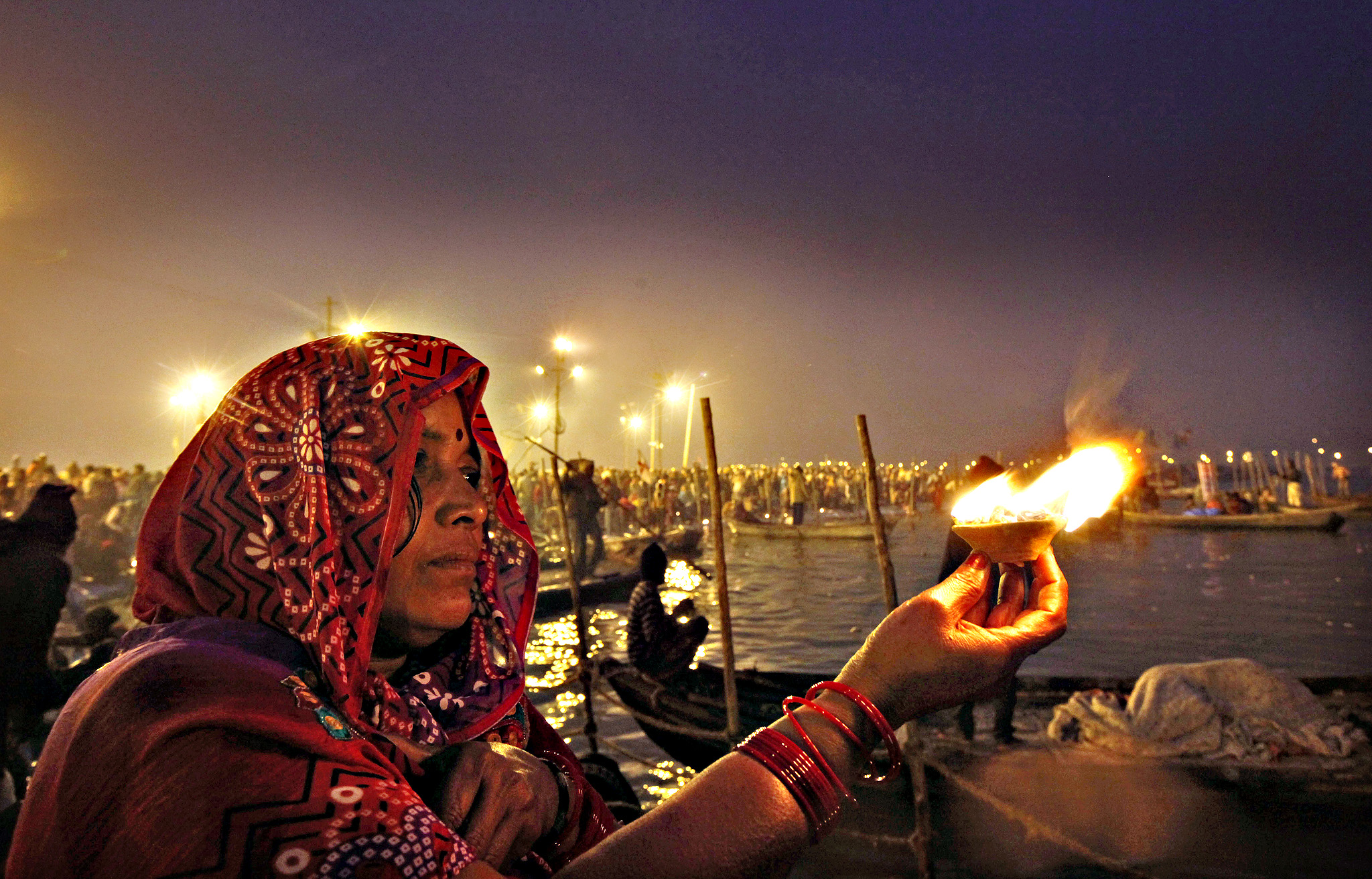 "A Hindu woman devotee holds an oil lamp and offers prayers to the Sun god after taking a holy dip at the Sangam, the confluence of the Ganges and Yamuna rivers, on ""Mauni Amavasya"" or new moon day, the third and most auspicious date of bathing during the annual month long Hindu religious fair ""Magh Mela"" in Allahabad, India,Tuesday, Jan. 20, 2015. Hundreds of thousands of Hindu pilgrims take dips in the confluence, hoping to wash away sins during the month long festival."