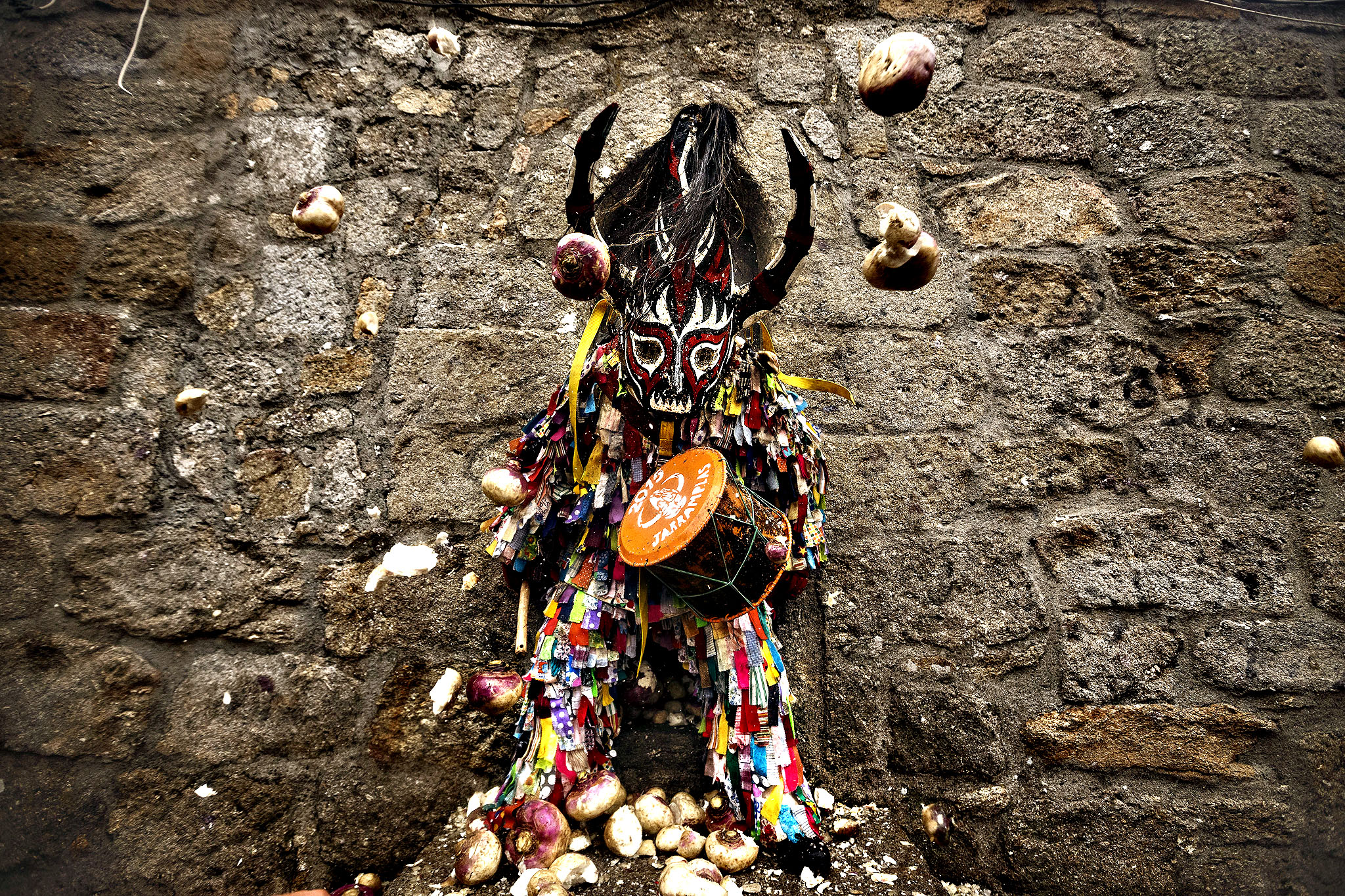 People throw turnips at the Jarramplas as he makes his way through the streets beating his drum during the Jarramplas Festival in Piornal, Spain, Tuesday, Jan. 20, 2015. Jarramplas is a character that wears a costume made from colorful strips of fabric, and a devil-like mask and beats a drum through the streets of Piornal while residents throw turnips as a punishment for stealing cattle. The exact origin of the festival are not known, various theories exist from the mythological punishment of Caco by Hercules, to a cattle thief ridiculed and expelled by his neighbors. The Jarramplas Festival takes place every year from the 19th till the 20th of January on Saint Sebastian Day.