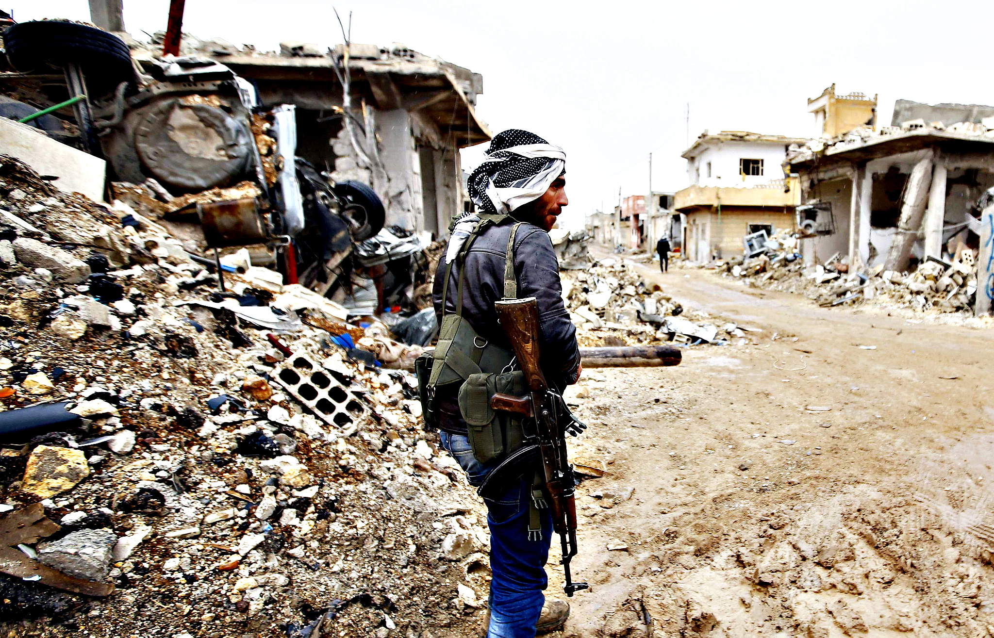 A fighter of the Kurdish People's Protection Units (YPG) stands next to damaged buildings in the northern Syrian town of Kobani January 30, 2015. Sheets meant to hide residents from snipers' sights still hang over streets in the Syrian border town of Kobani, and its shattered buildings and cratered roads suggest those who fled are unlikely to return soon. Kurdish forces said this week they had taken full control of Kobani, a mainly Kurdish town near the Turkish border, after months of bombardment by Islamic State, an al Qaeda offshoot that has spread across Syria and Iraq.