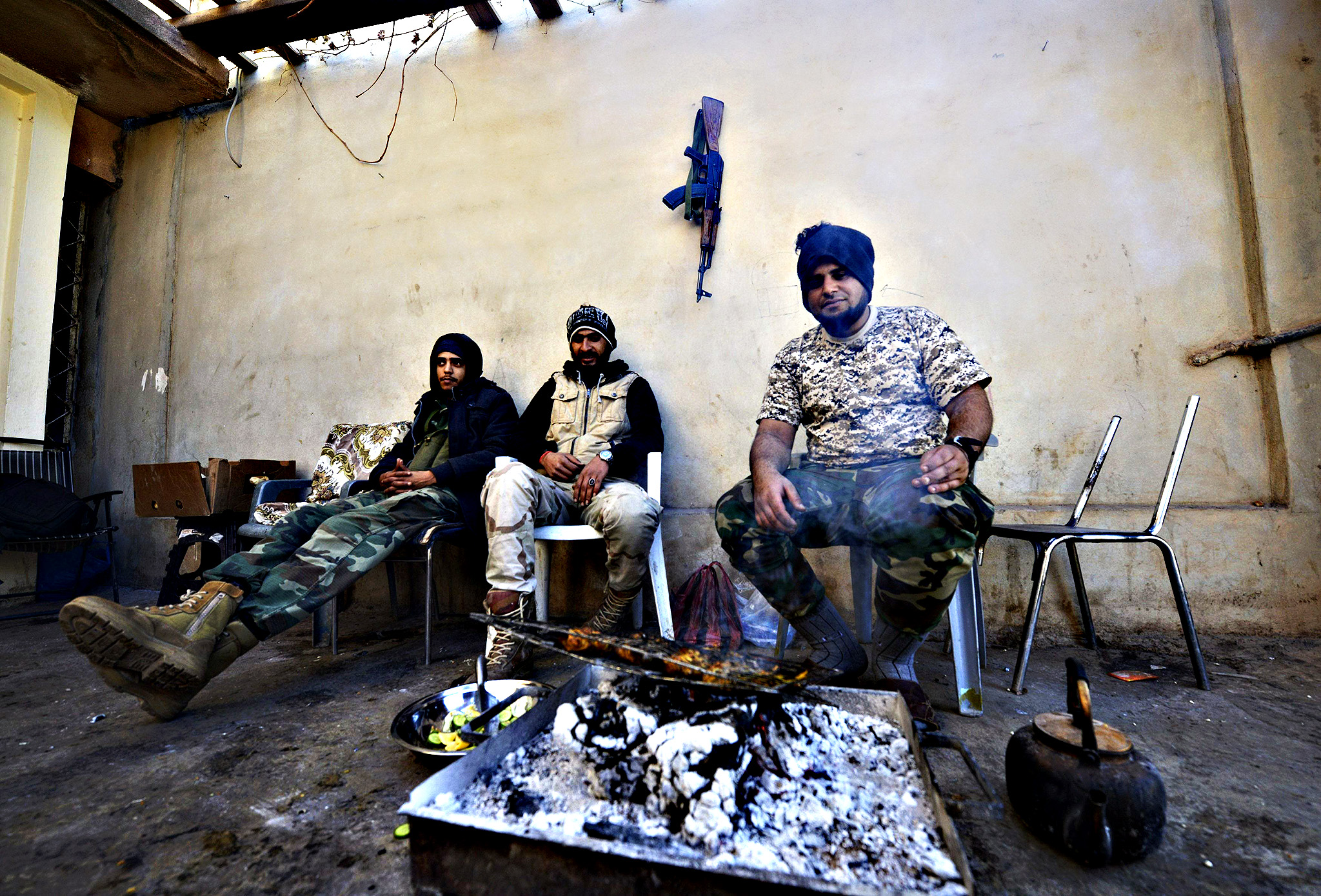 Members of Libyan pro-government forces, who are backed by the locals, sit together during clashes with the Shura Council of Libyan Revolutionaries in Benghazi...Members of Libyan pro-government forces, who are backed by the locals, sit together during clashes with the Shura Council of Libyan Revolutionaries in the streets of Benghazi January 19, 2015. The Shura Council of Libyan Revolutionaries is an alliance of former anti-Gaddafi rebels who have joined forces with Islamist group Ansar al-Sharia