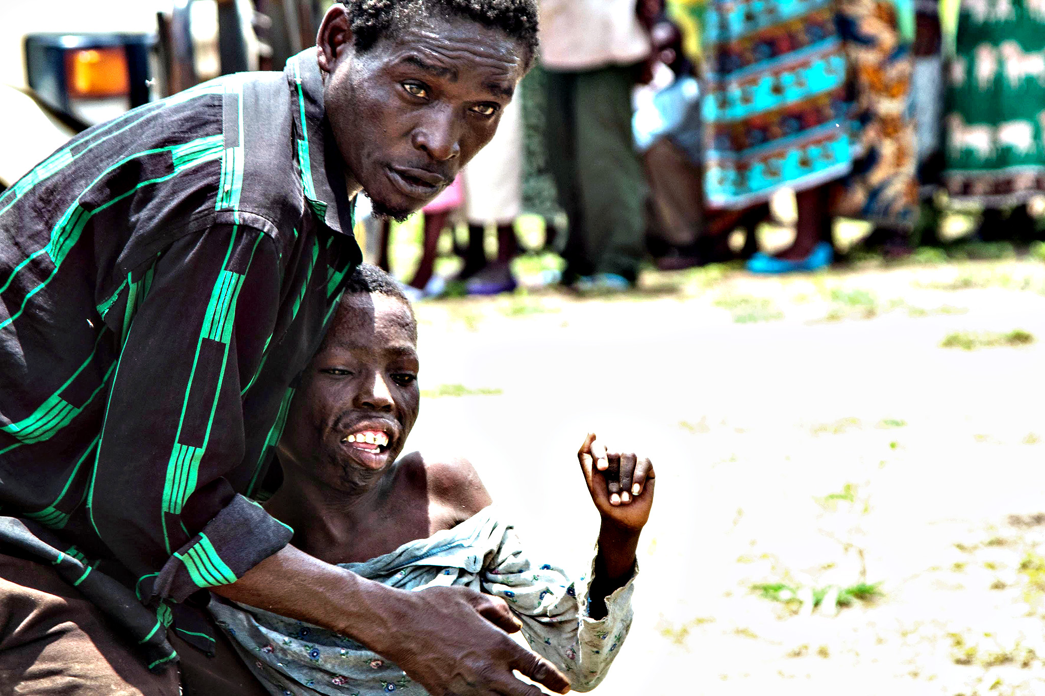 A flood victim attempting to help his disabled child at a food hand-out point in Nchalo, Malawi. The Malawi government has declared half the country a disaster zone after torrential rains killed at least 170 people, left an estimated 100,000 homeless, and destroyed bridges and roads. The death toll had earlier been given as 48. It rose after villagers in the southern district of Nsanje were swept away by swelling rivers. Meteorologists warned that rains could continue for days.