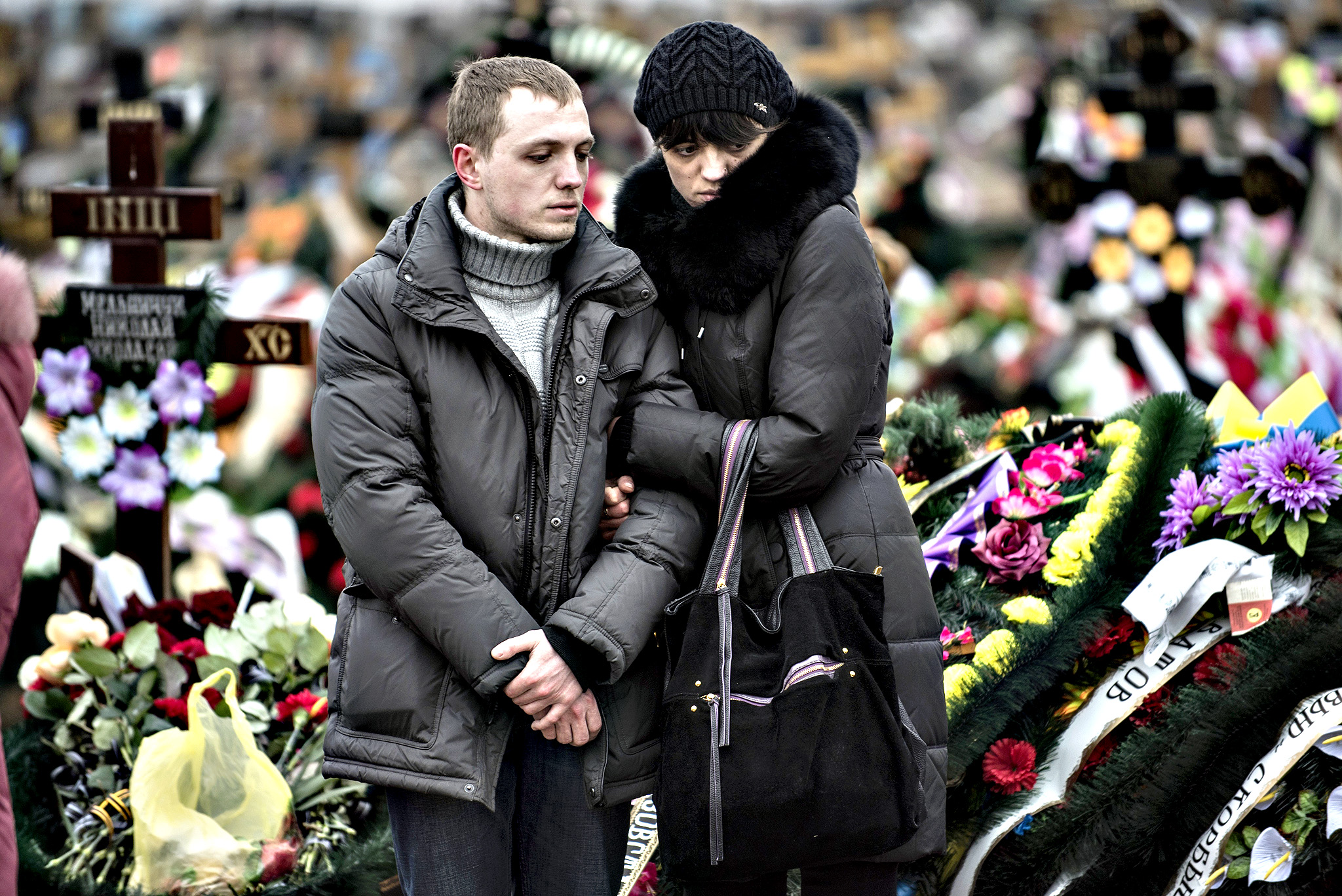 Relatives of Alexander Demyanenko, a victim of Saturday's shelling, stand near a grave during funerals in Mariupol, Ukraine, on Monday Jan. 26, 2015. At least 5,100 people have been killed in eastern Ukraine since fighting began in April, but violence this week was the most intense since a cease-fire deal was signed in September.