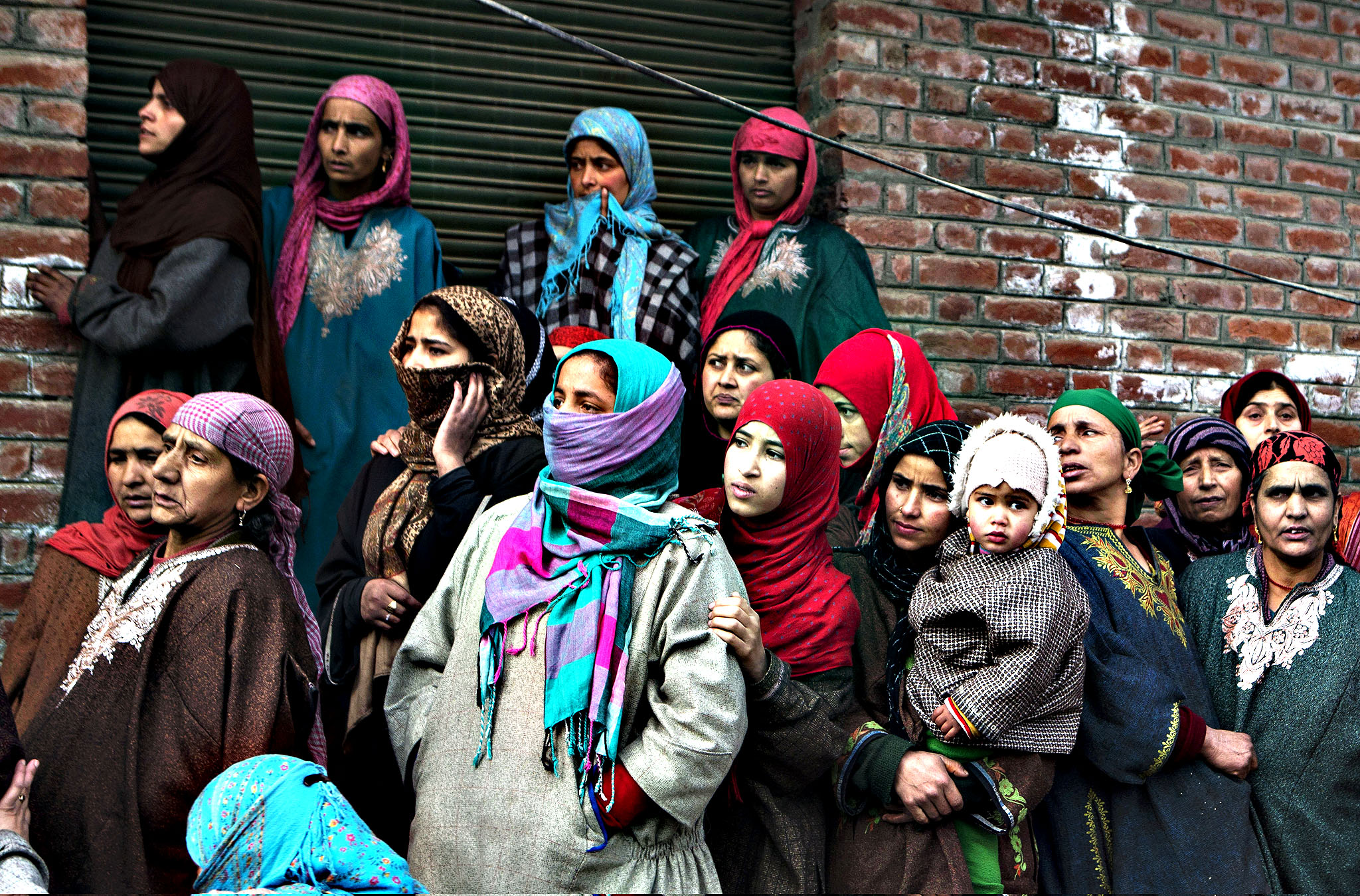 Kashmiri Muslim women watch the funeral procession of Ishfaq Ahmed Malik, a suspected local militant, in Arwani, some 55 kilometers (35 miles) south of Srinagar, India, Friday, Jan. 16, 2015. Indian soldiers and police killed five suspected rebels during a fierce gunbattle Thursday in the disputed Himalayan region of Kashmir, officials said.
