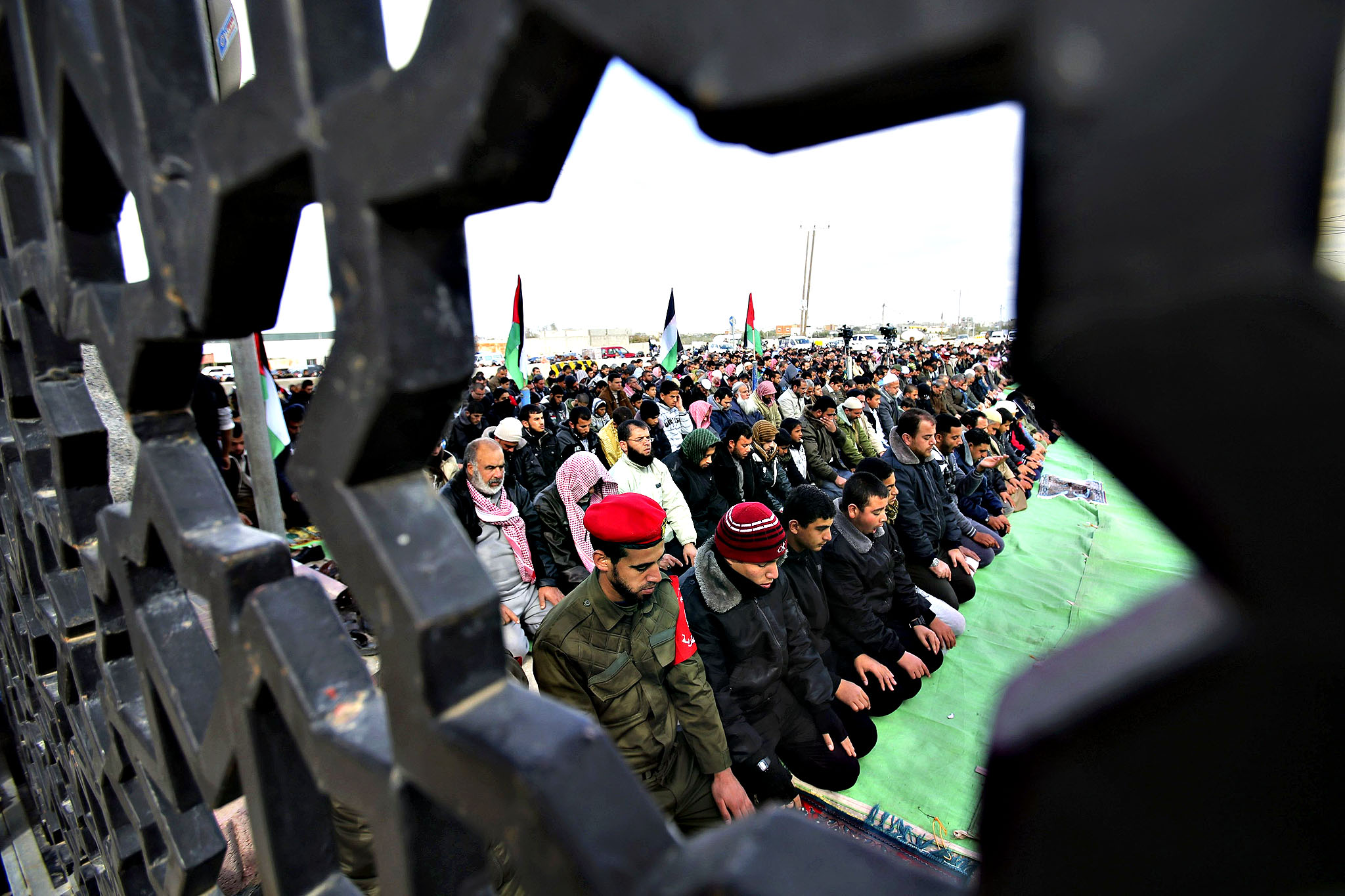 Palestinians are pictured through a gate as they perform Friday prayers at the Rafah border crossing between Egypt and southern Gaza Strip January 16, 2015, to demand that Egyptian authorities open the crossing.  Egypt shut Rafah crossing, Gaza's main window to the outside world, over violence with Islamist militants in Egypt's adjacent Sinai region last October. Since then, it opened the crossing for a few days to allow thousands of Palestinians get in and out of Gaza Strip.