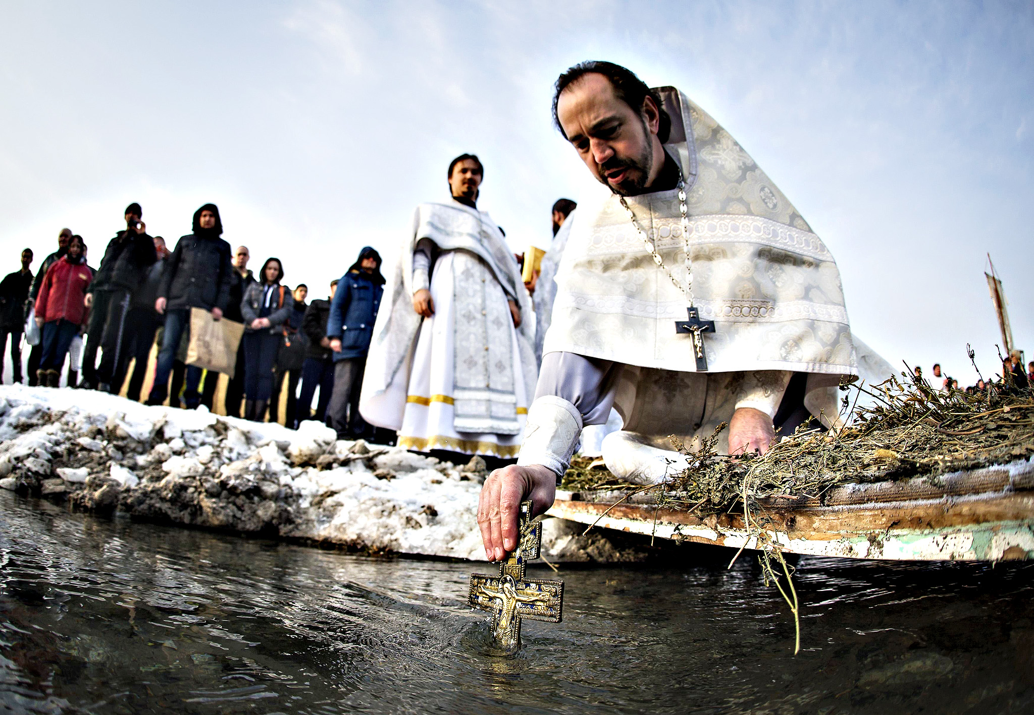 An Orthodox priest immerses a cross in the Bolshaya Almatinka river to bless its water during an Epiphany ceremony in Almaty January 19, 2015. Orthodox believers abiding by the Julian calendar mark Epiphany on January 19 by immersing themselves in icy waters regardless of the weather.