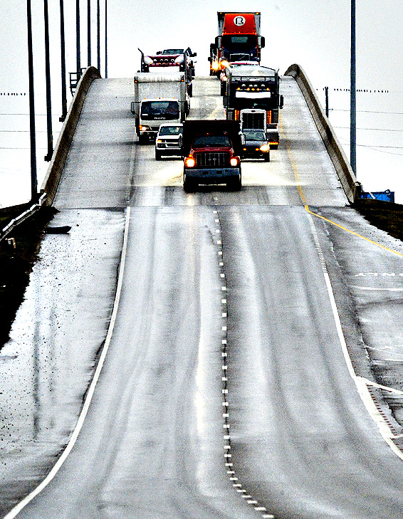 A truck from the Alabama Department of Transportation, followed by traffic, spreads sand on the northbound lanes of the Hudson Memorial Bridge spanning the Tennessee River, Thursday, Jan. 15, 2015, in Decatur, Ala.   A wintery mix of precipitation was expected throughout the day.