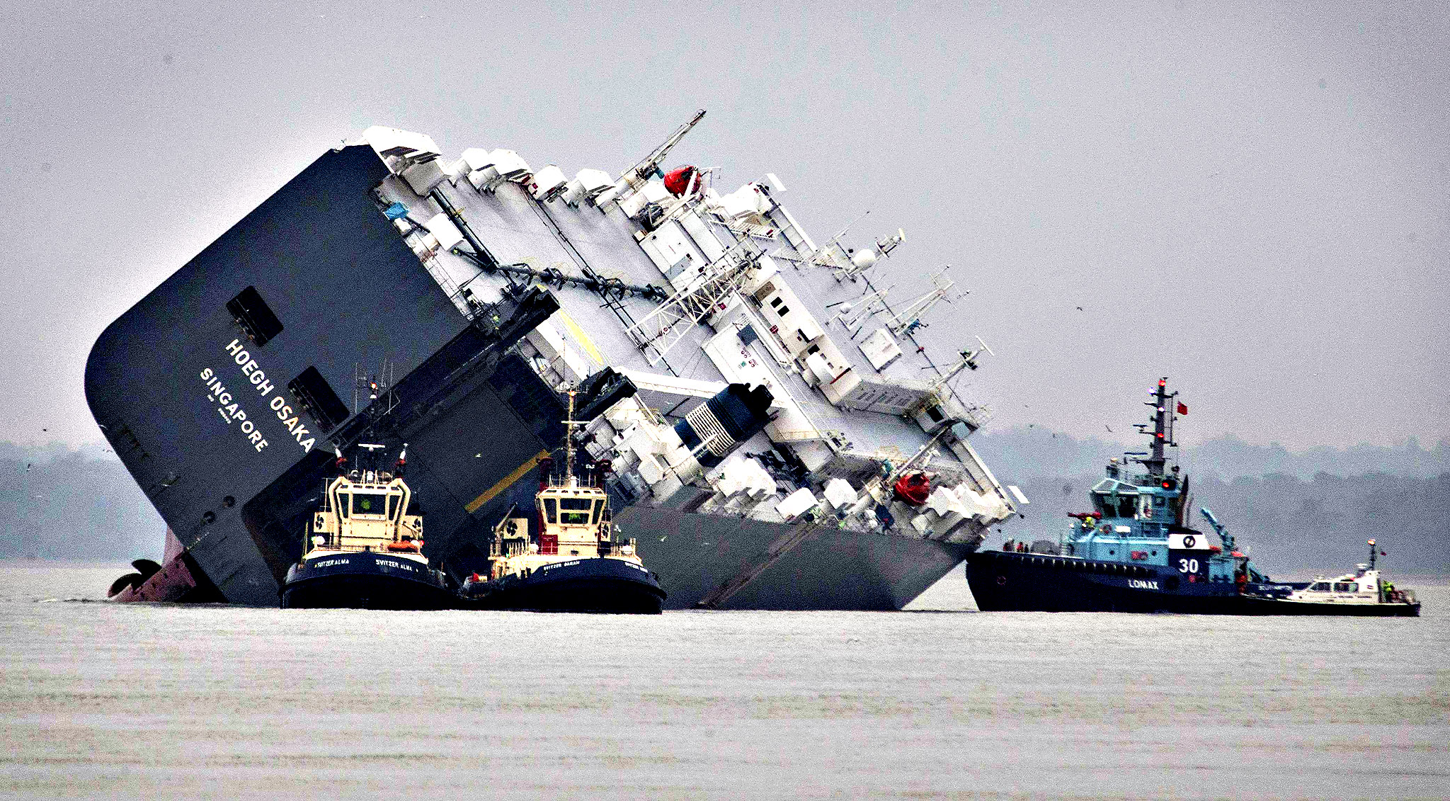 The cargo ship Hoegh Osaka lies on its side after being deliberately ran aground on the Bramble Bank in the Solent estuary, near Southampton in southern England January 5, 2015. The vessel was deliberately run aground on Saturday evening after it began to list, according to its owners Hoegh Autoliners.