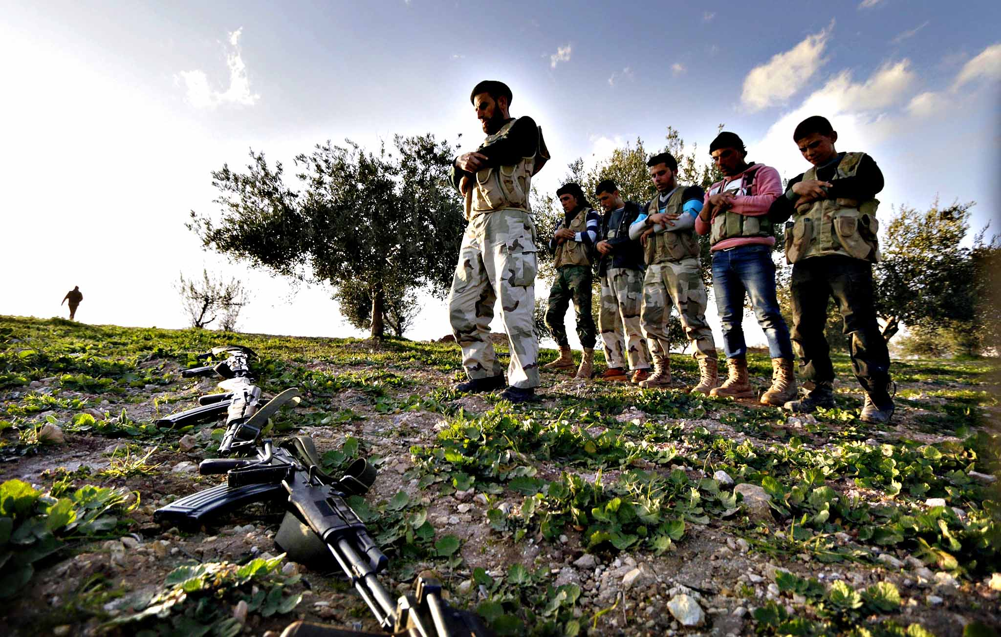 Rebel fighters pray beside the al-Sayyad hill bordering the town of Morek in the northern countryside of Hama