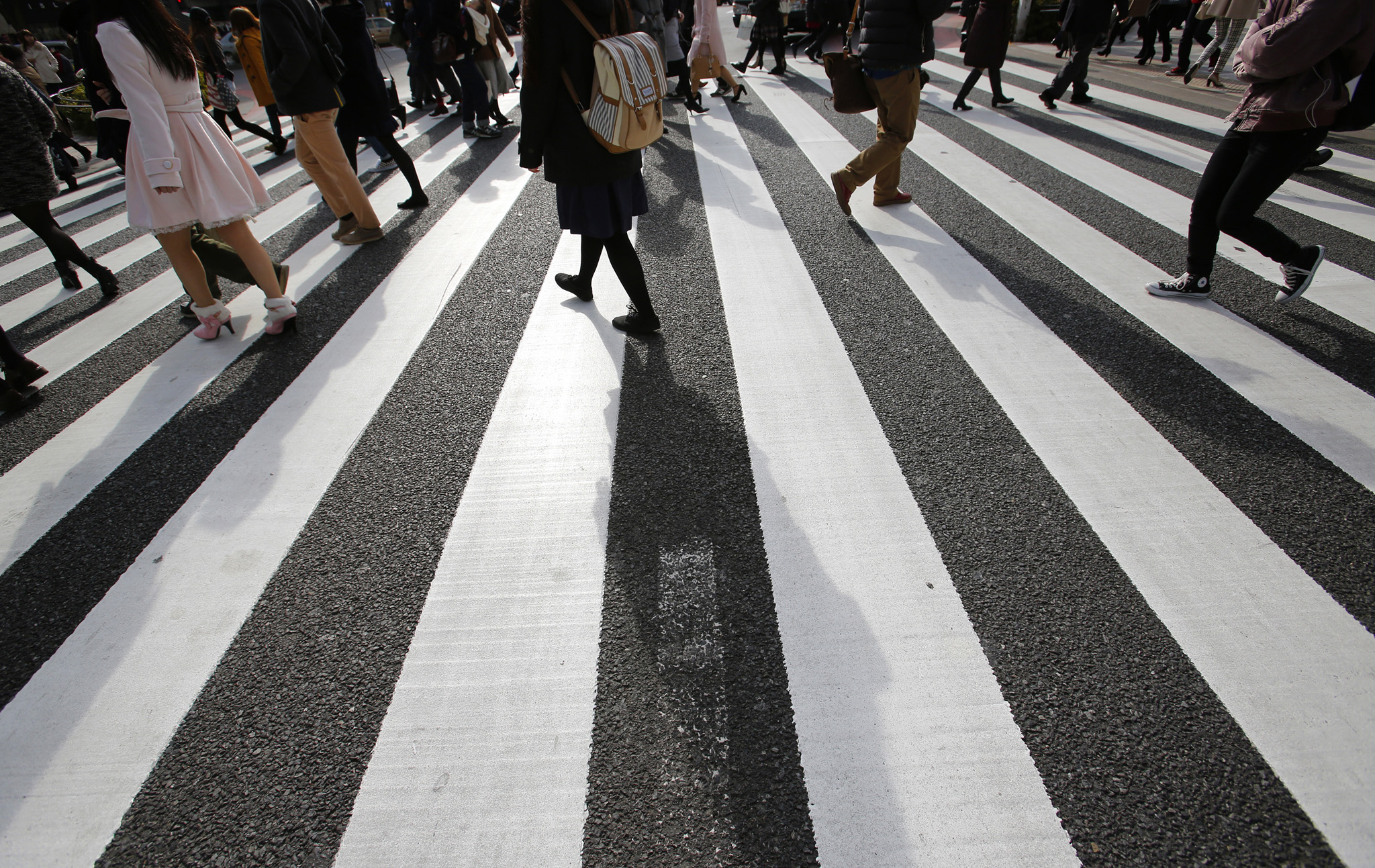 People walk on a pedestrian crossing in Tokyo Wednesday, Jan. 14, 2015. Japan's Cabinet approved a record 96.3 trillion yen ($814 billion) government budget for the coming fiscal year Wednesday after a tax hike to accommodate rising outlays for social security and defense. Rising revenues following the sales tax increase last April enabled Prime Minister Shinzo Abe to raise spending without increasing the proportion financed by new government bonds, though the total national debt is still about twice the size of the economy