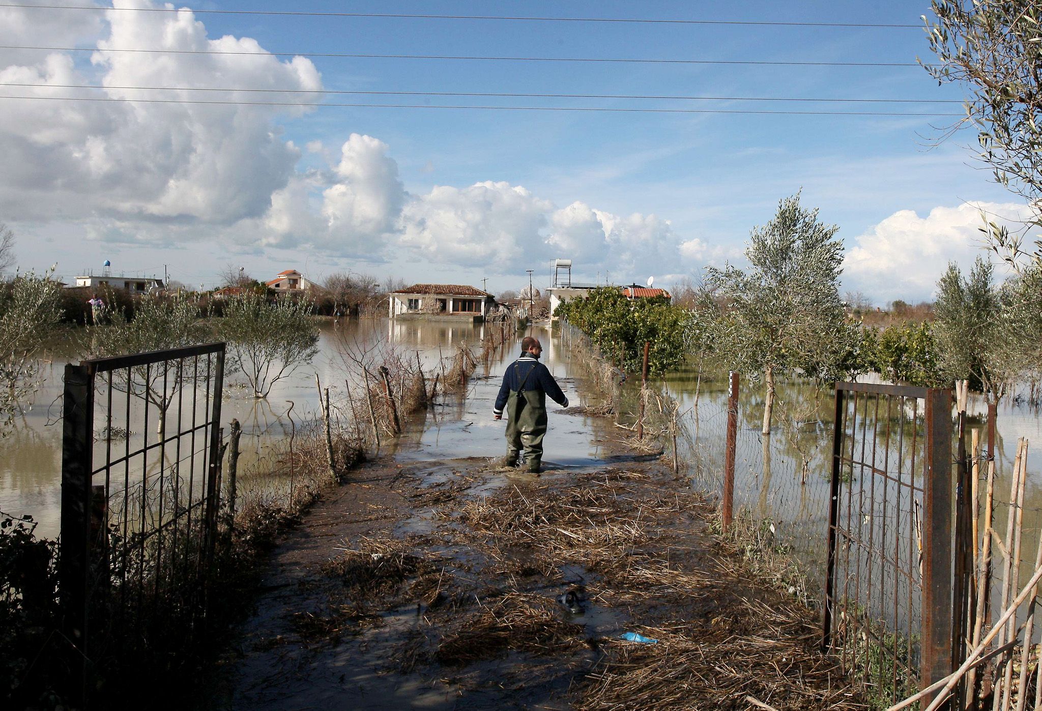 An Albanian man walks through flood waters towards his home in the village of Mifol near the city of Vlora on February 3, 2015. Floods caused by heavy rains over the last days have hit southern Albania, forcing the evacuation of hundreds of villagers after rivers flooded thousands of hectares (acres), hundreds of homes and many roads. Many regions in southern Albania had no power or water. Police urged residents to cancel travel plans and more intense rain was forecast to hit over the next few days. No casualties were reported. AFP PHOTO / GENT SHKULLAKUGENT SHKULLAKU/AFP/Getty Images
