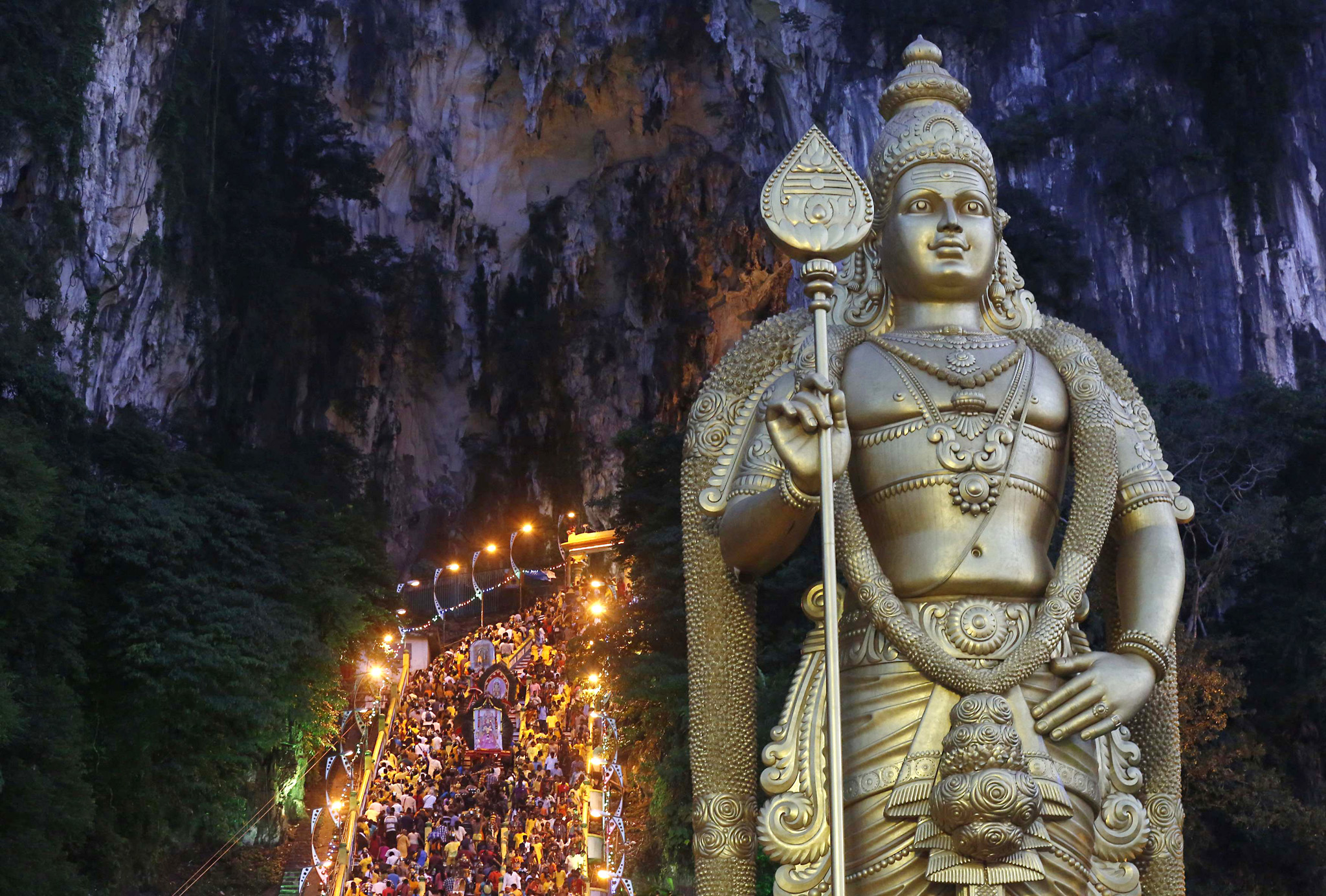 Hindu devotees climb the steps to Batu Caves temple during Thaipusam in Kuala Lumpur...Hindu devotees climb the steps to Batu Caves temple during Thaipusam in Kuala Lumpur February 3, 2015. Hindu devotees across Malaysia on Tuesday celebrated Thaipusam, a religious celebration dedicated to the Hindu deity Lord Murugan. Piercing various parts of their body with silver skewers, devotees carry often large contraptions known as Kavadi, thereby taking on a physical burden through which the devotees implore for help from Murugan. Devotees also fulfill vows by carrying milk-filled pots up the stairs to the cave temple. REUTERS/Olivia Harris (MALAYSIA - Tags: SOCIETY RELIGION TPX IMAGES OF THE DAY)