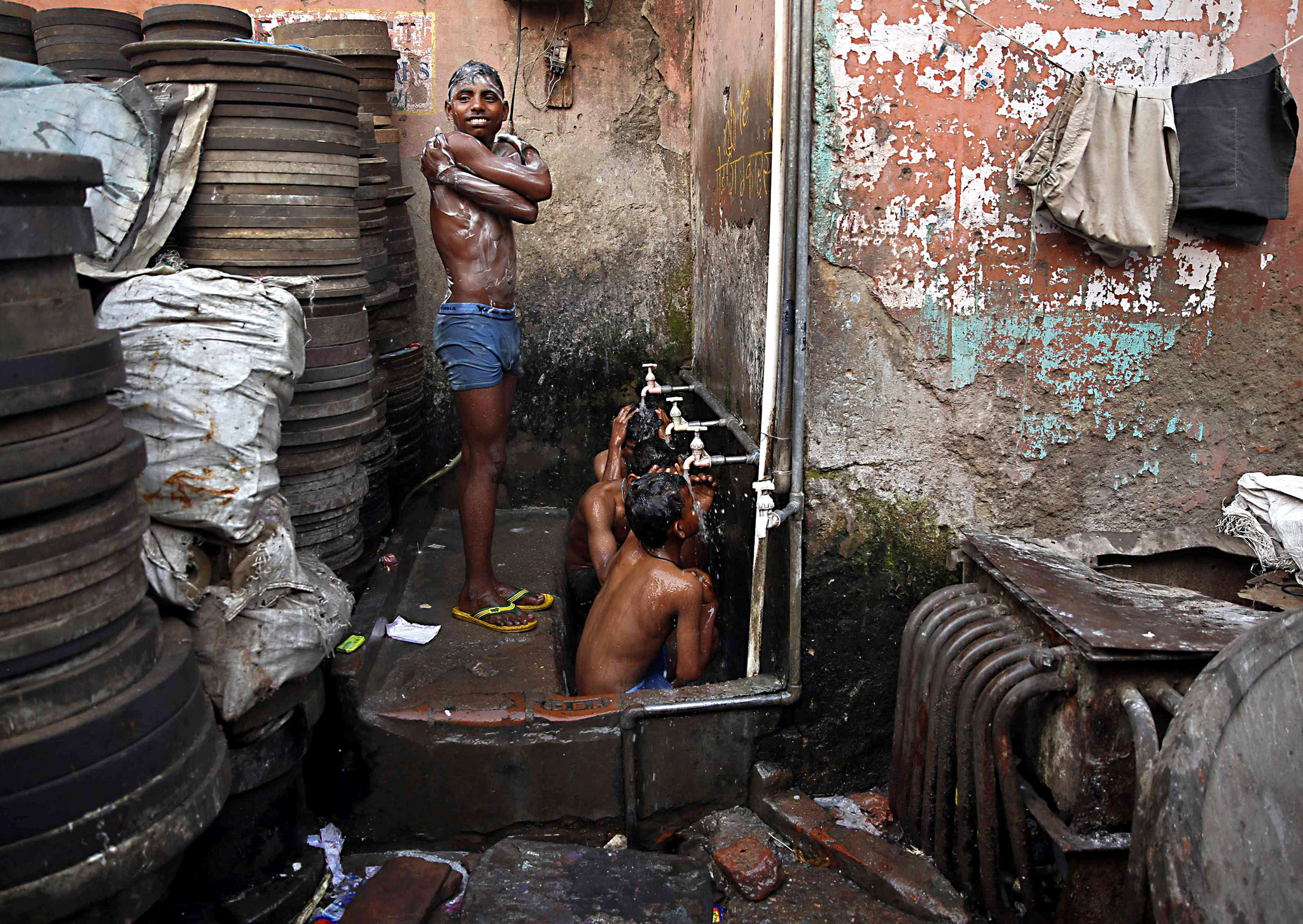 Boys bathe at roadside municipal taps during early morning in the old quarters of Delhi...Boys bathe at roadside municipal taps during early morning in the old quarters of Delhi February 17, 2015. REUTERS/Ahmad Masood (INDIA - Tags: SOCIETY)