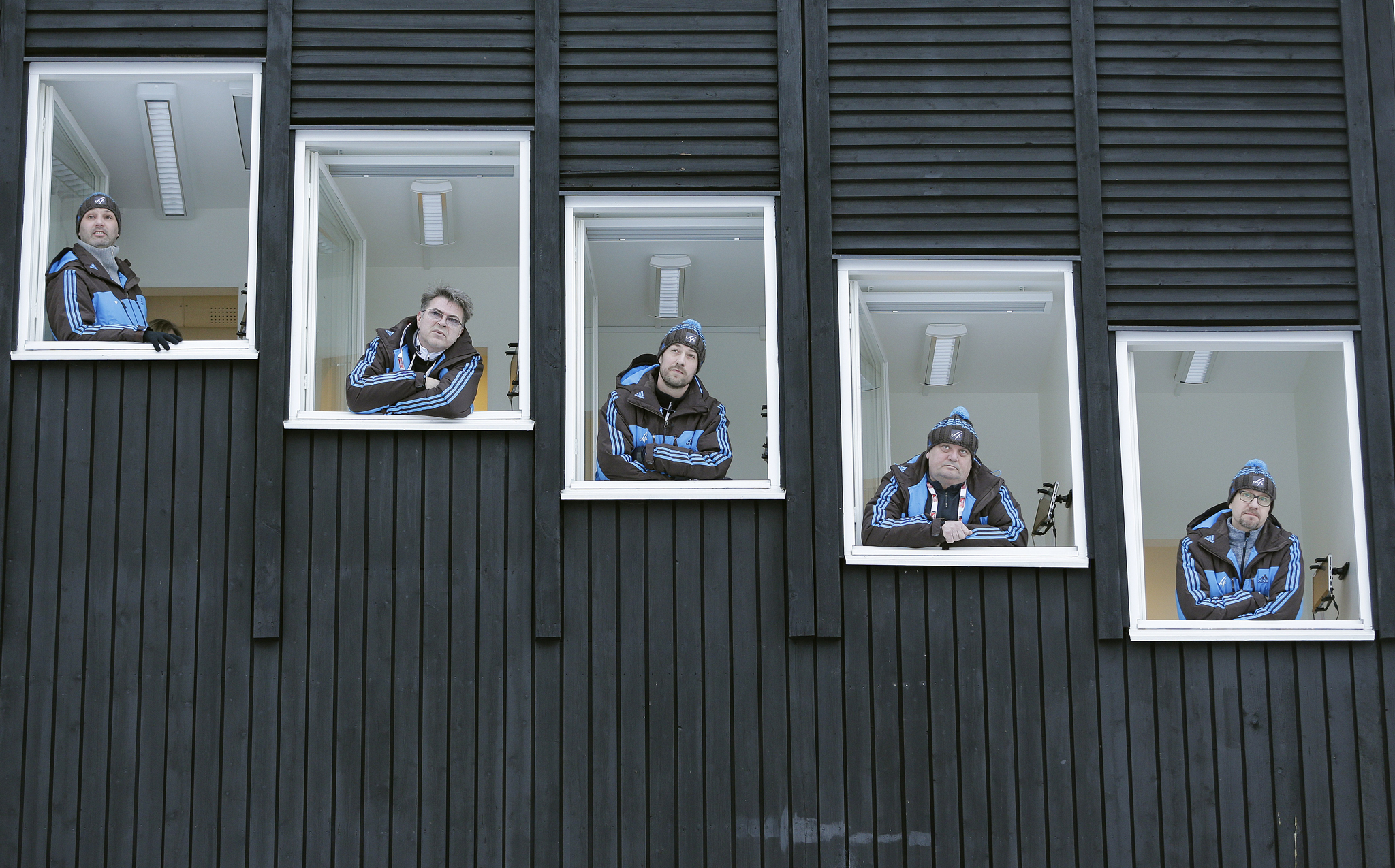 Judges of the normal hill ski jumping competition look out of windows at the Nordic Skiing World Championships in Falun, Sweden, Friday, Feb. 20, 2015. The individual competition was shifted to later in the day due to heavy winds. (AP Photo/Matthias Schrader)