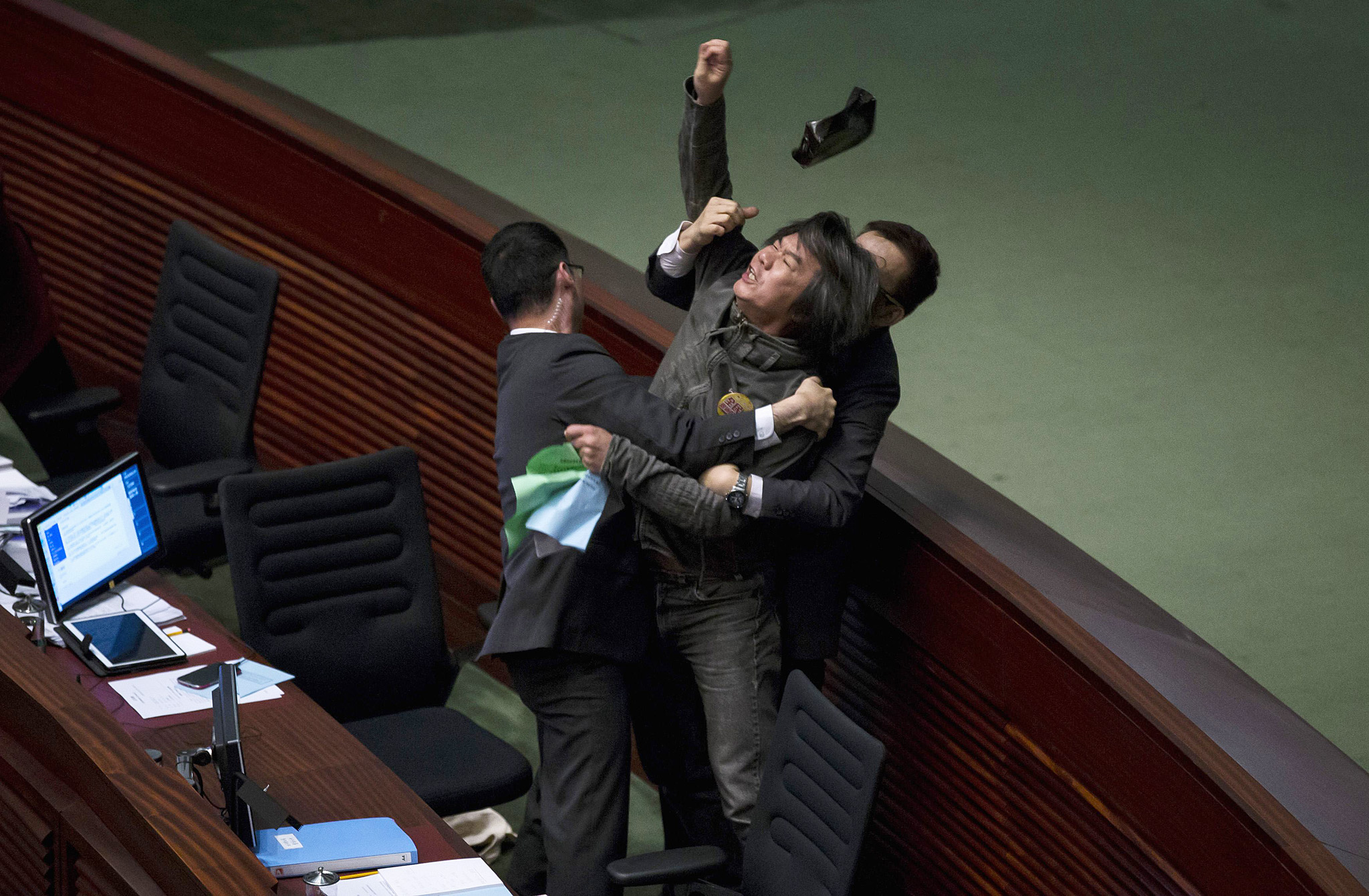 Pro-democracy lawmaker Leung Kwok-hung demands a universal retirement protection scheme during the annual budget report at the Legislative Council in Hong Kong...Pro-democracy lawmaker Leung Kwok-hung throws an object at Hong Kong's Financial Secretary John Tsang (not pictured) to demand a universal retirement protection scheme during the annual budget report at the Legislative Council in Hong Kong February 25, 2015. Hong Kong announced measures totalling HK$290 million ($37 million) on Wednesday to help businesses hit by more than two months of pro-democracy protests as the government seeks to rebuild confidence in the Asia financial centre. REUTERS/Tyrone Siu (CHINA - Tags: POLITICS BUSINESS CIVIL UNREST TPX IMAGES OF THE DAY)