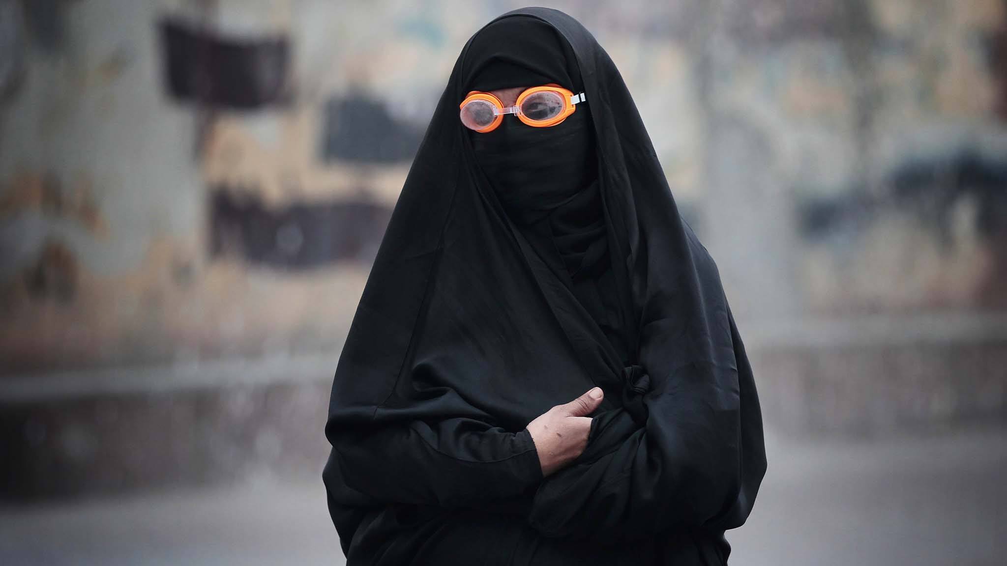 Female protester wearing goggles stands on a street during clashes in the village of Bilad Al Qadeem