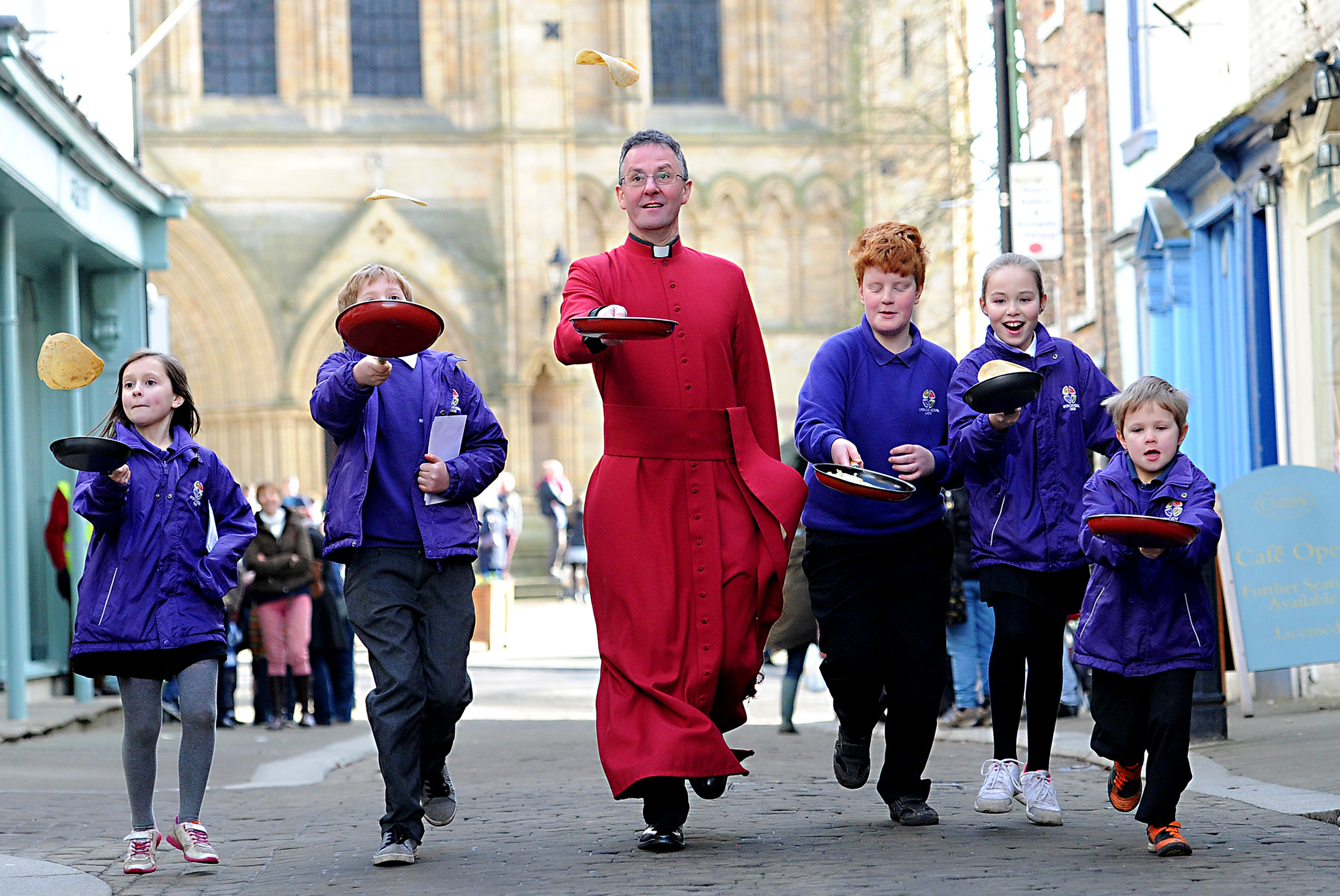 he Dean of Ripon Cathedral John Dobson takes part in the annual Pancake Races with children from Ripon Cathedral School outside Ripon Cathedral, North Yorkshire. PRESS ASSOCIATION Photo. Issue date: Tuesday February 17, 2015. Photo credit should read: Anna Gowthorpe/PA Wire