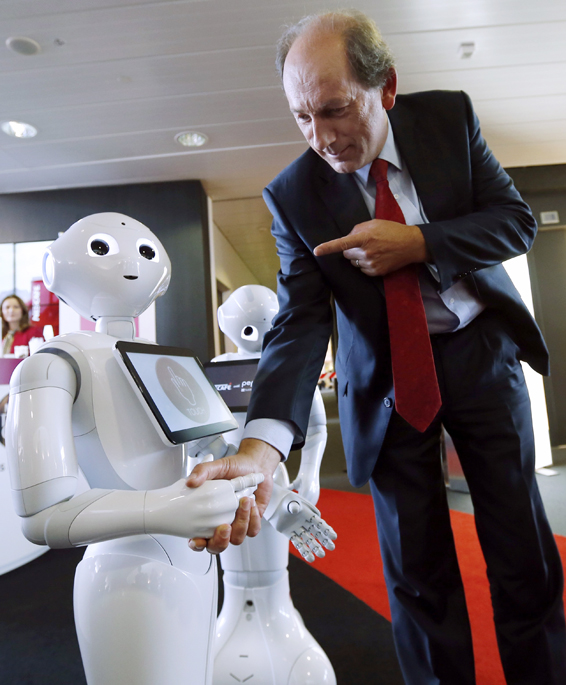 "Nestle CEO Bulcke interacts with a robot named ""Pepper"" after the full year 2014 results conference in Vevey...Nestle Chief Executive Officer (CEO) Paul Bulcke (R) interacts with a robot named ""Pepper"" after the full year 2014 results conference at the company headquarters in Vevey February 19, 2015. Nestle in December 2014 began to use the robots to help sell its coffee makers at electronics stores across Japan, becoming the first corporate customer for the chatty, bug-eyed androids unveiled in June 2014 by tech conglomerate SoftBank Corp. REUTERS/Denis Balibouse"