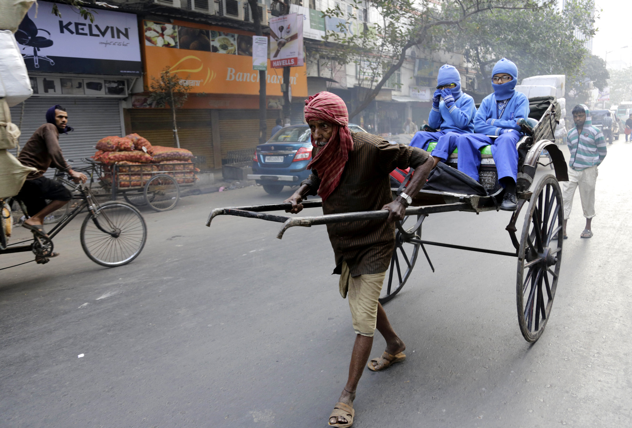 An Indian hand rickshaw puller transports children to school in Kolkata, India, Tuesday, Feb. 10, 2015. Kolkata is the only city in India where hand-pulled rickshaws are still in operation. (AP Photo/Bikas Das)