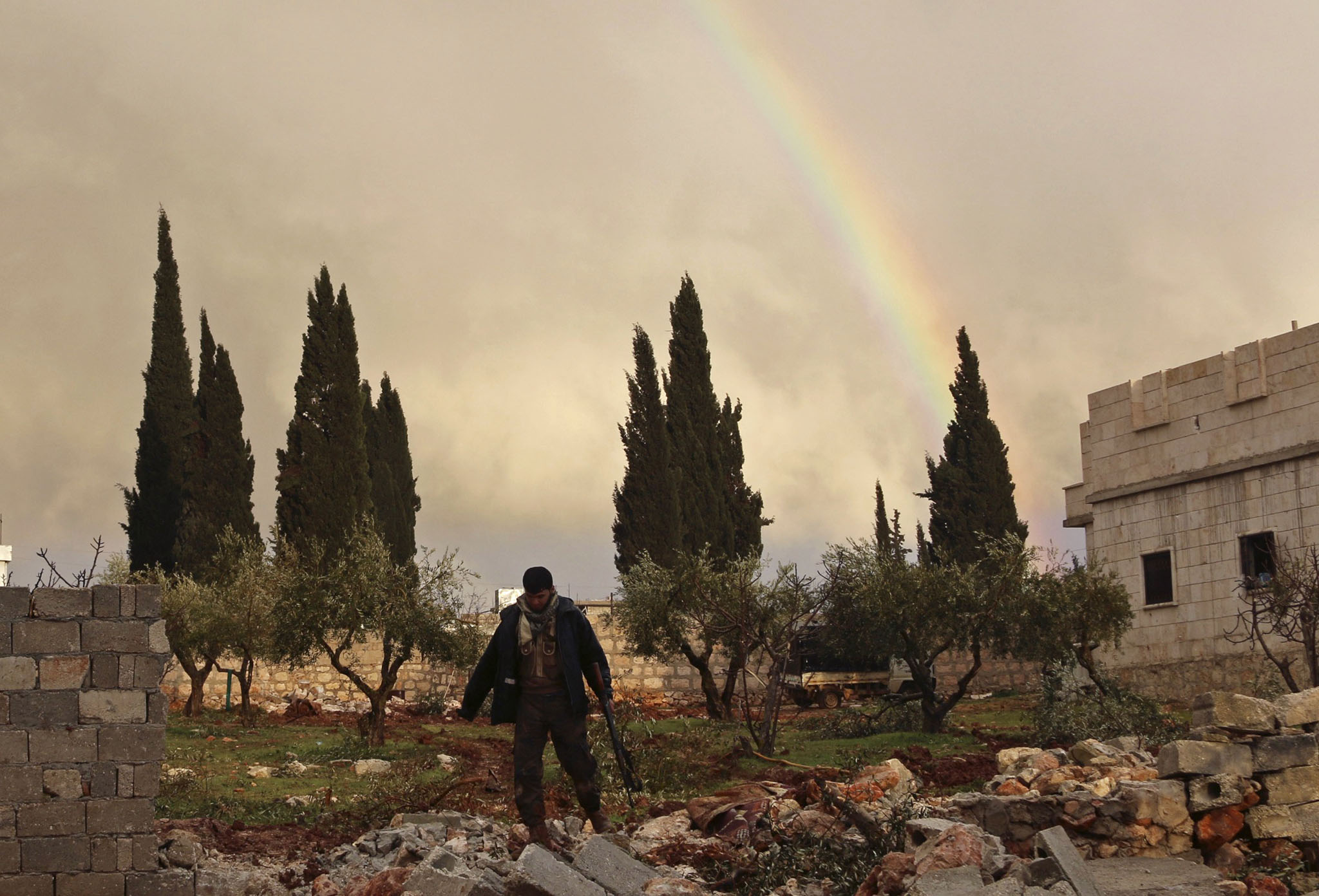 A rebel fighter carries his weapon as he walks in front of a rainbow in Ratian village, north of Aleppo...A rebel fighter carries his weapon as he walks in front of a rainbow in Ratian village, north of Aleppo, after what the rebels said was an offensive against them by forces loyal to Syria's President Bashar al-Assad that attempted to advance in the village but failed to February 18, 2015. Battles in and around the Syrian city of Aleppo have killed at least 70 pro-government fighters and more than 80 insurgents after the army launched an offensive there, a monitoring group said on Wednesday. Picture taken February 18, 2015. REUTERS/Ammar Abdullah    (SYRIA - Tags: POLITICS CIVIL UNREST CONFLICT)